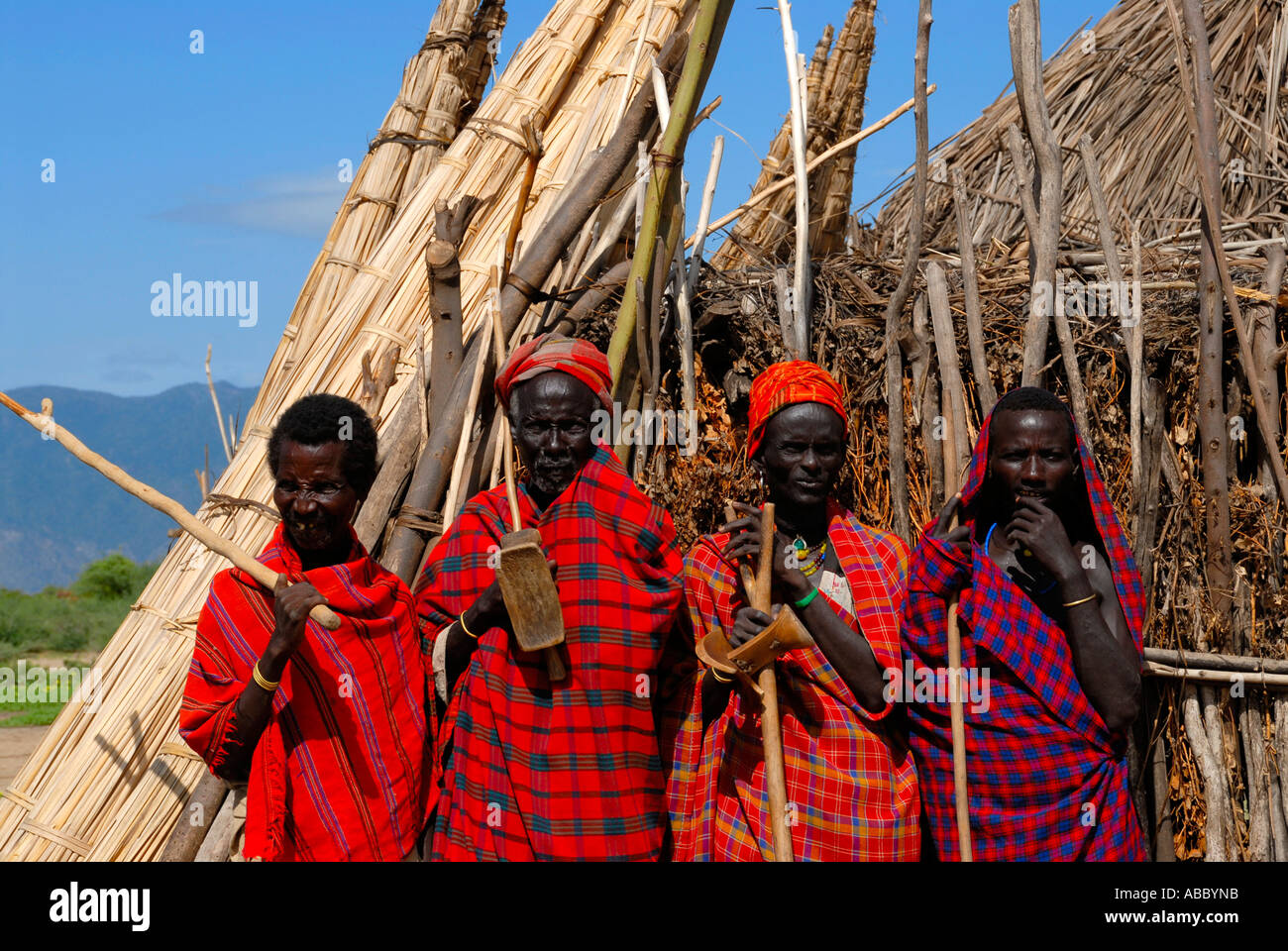 Four men chiefs elders of the Arbore people dressed in red capes in front of a hut Ethiopia - Stock Image