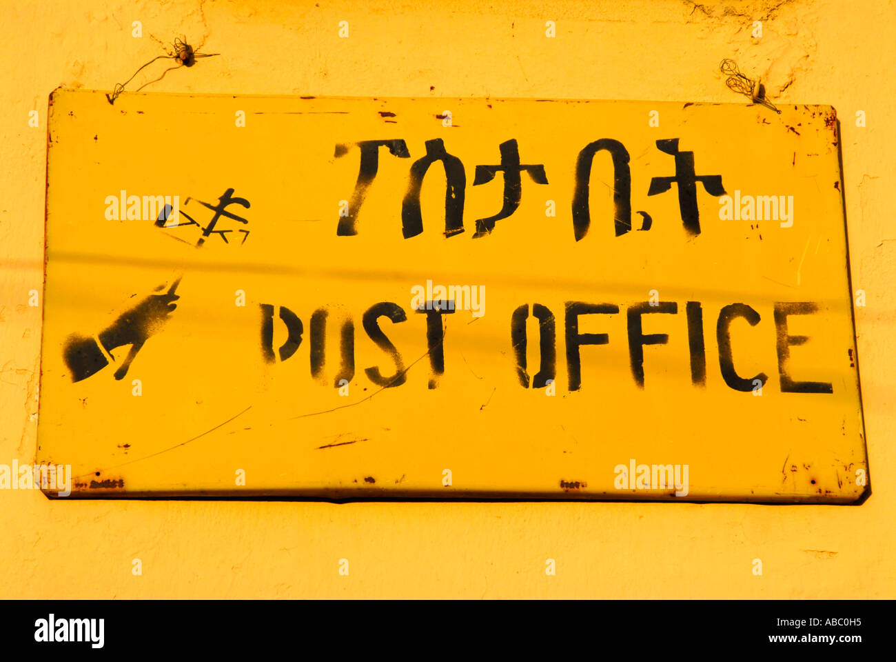 Yellow sign at post office with Amharic script Axum Ethiopia - Stock Image
