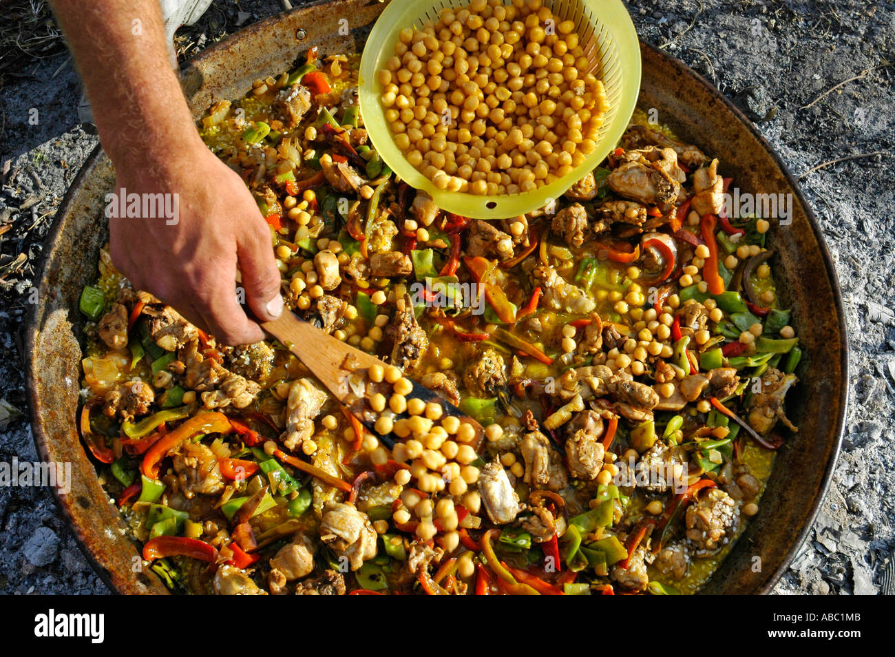 Chickpeas are added while cooking a Paella in a pan, spanish speciality, Spain - Stock Image