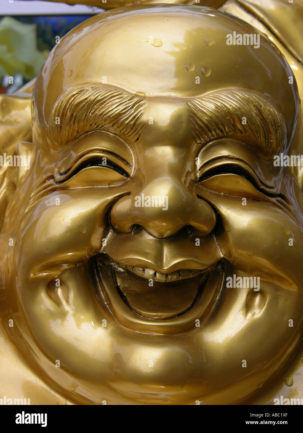 Portrait of a laughing golden Buddah figure - Stock Image