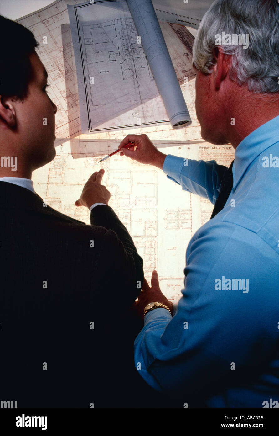 Architecture / Business - Architects, businessmen, executives inspecting, reviewing, examining blueprints on a light table. - Stock Image