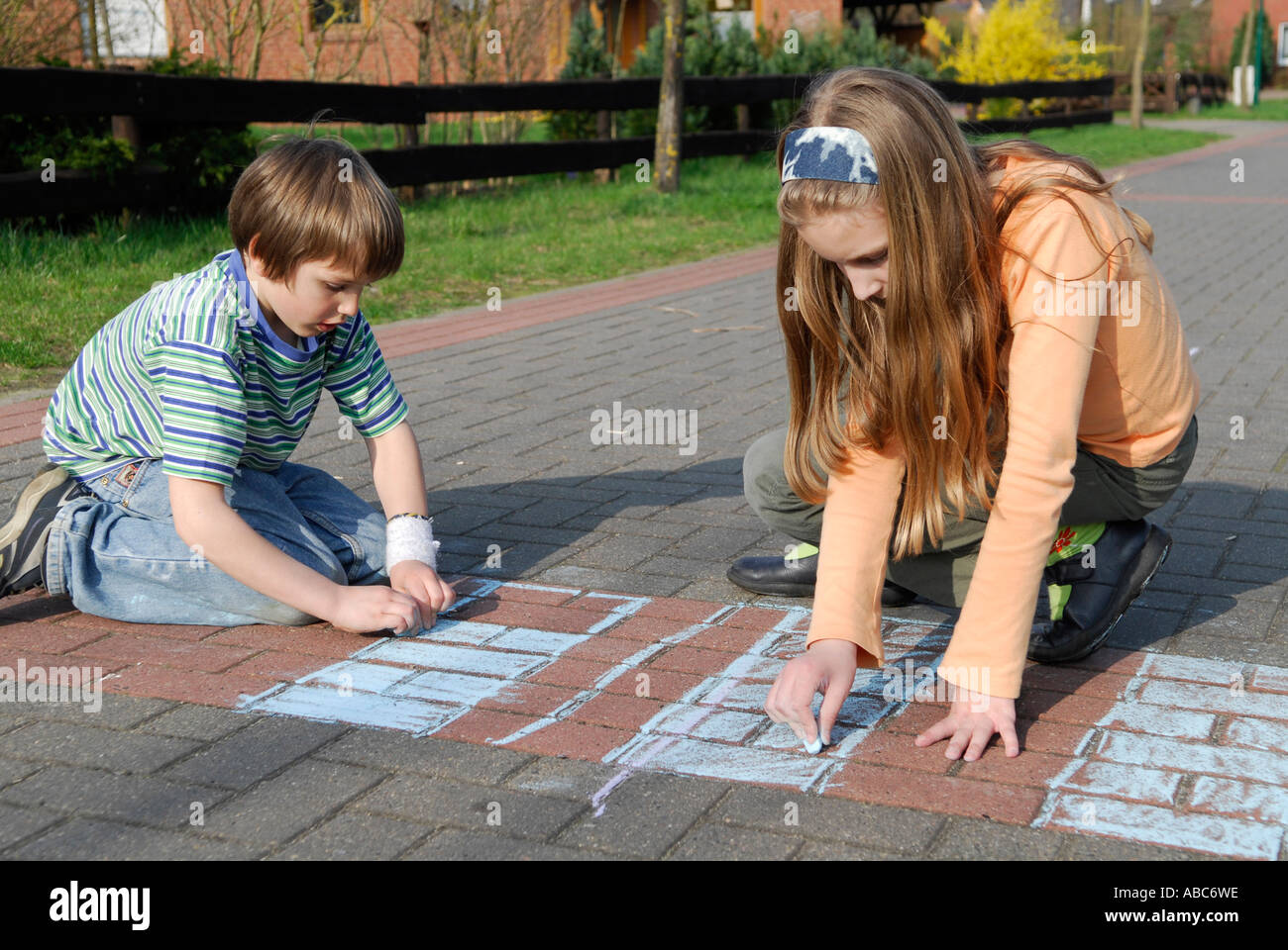 Children paint with chalk on the road - Stock Image