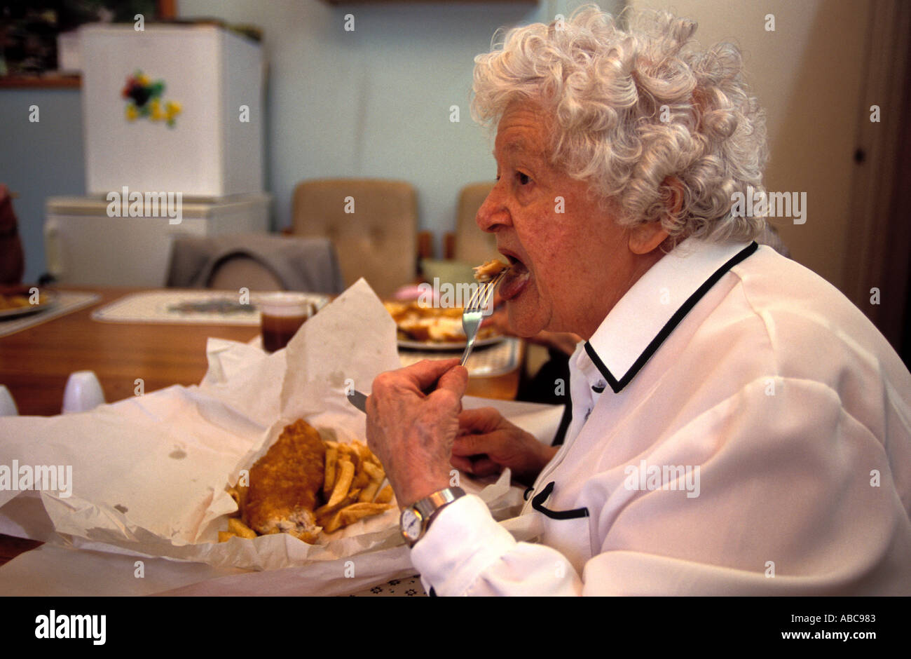 Elderly woman in sheltered housing eating fish and chips, Lambeth, London, UK. - Stock Image