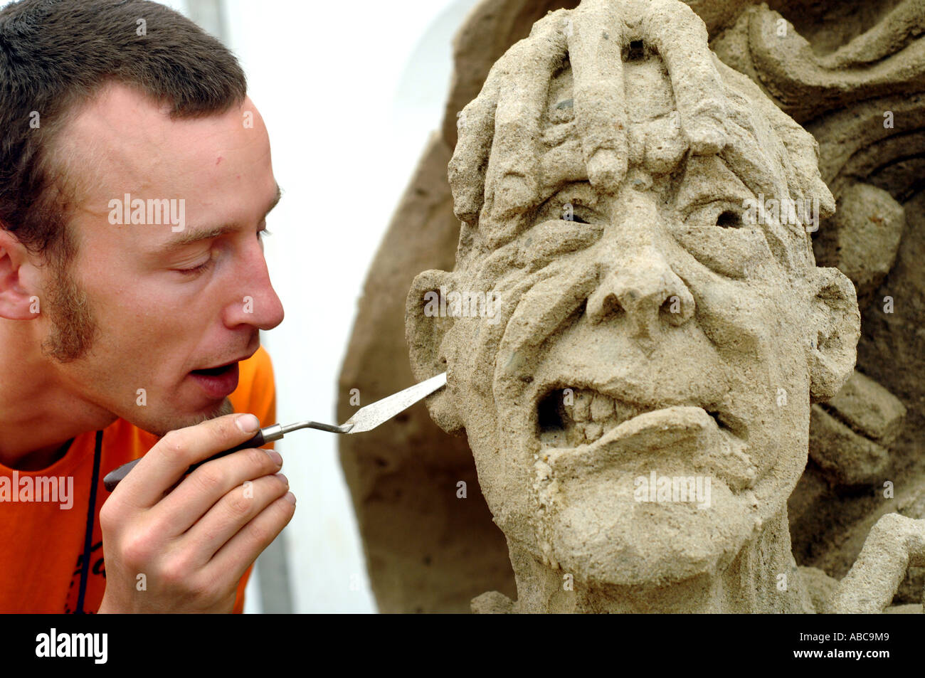 Now this won't hurt a bit. A sand sculptor creates a grotesque figure as part of a display based on the Roman Empire - Stock Image