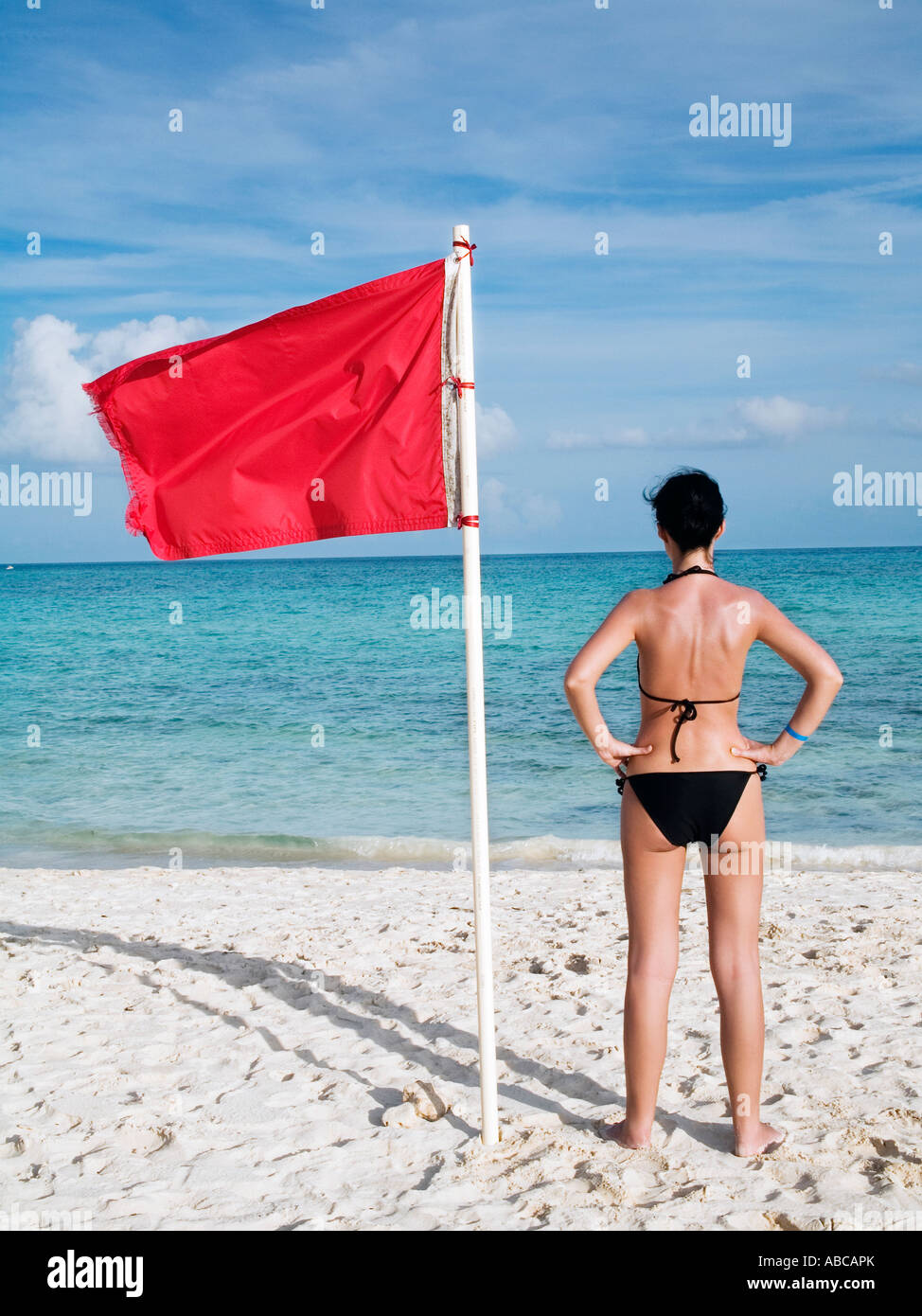 woman standing on te beach near a red flag on the sea meaning that swimming is dangerous and prohibited - Stock Image