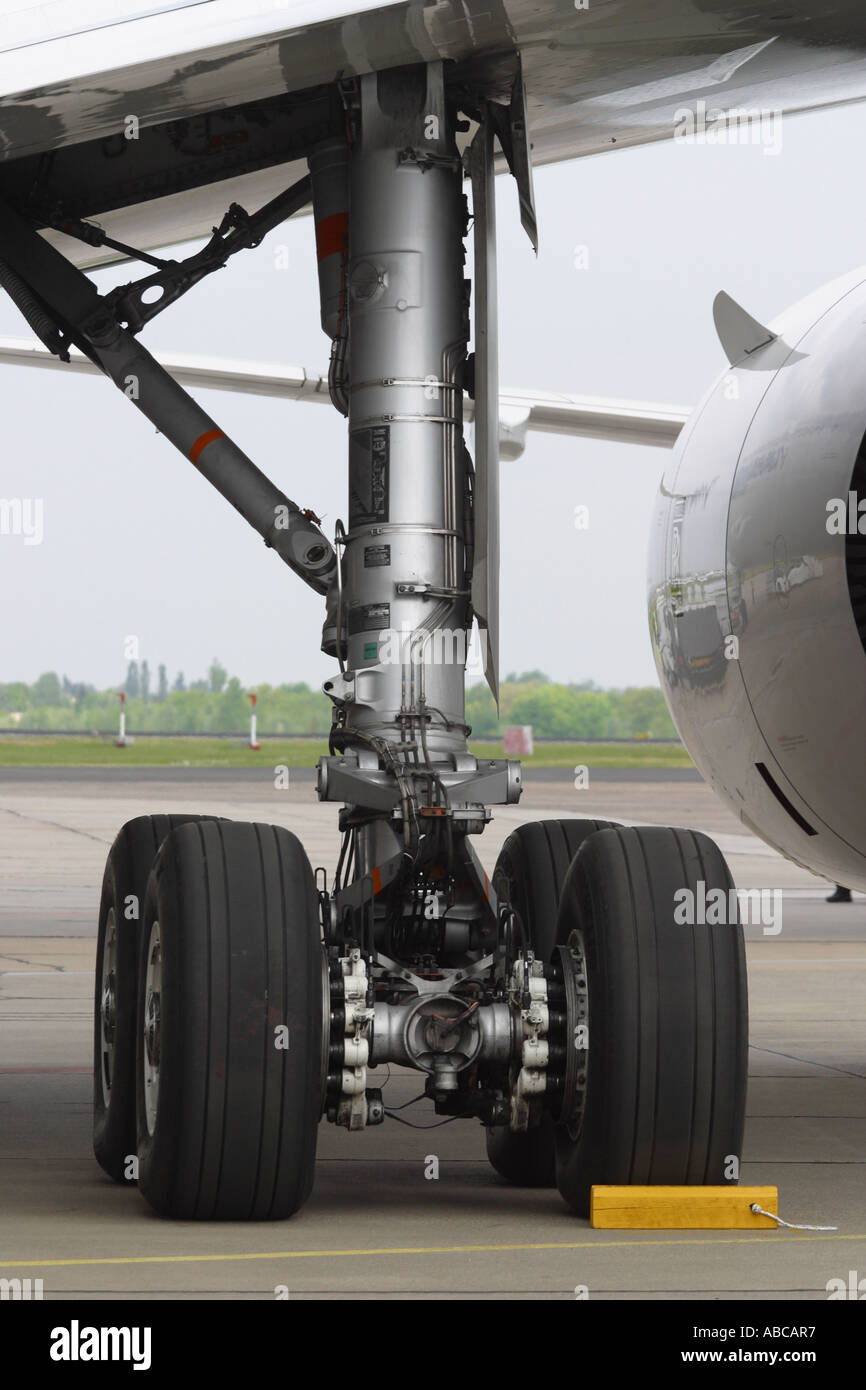 Airliner undercarriage leg main gear wheel tyre with chocks - Stock Image
