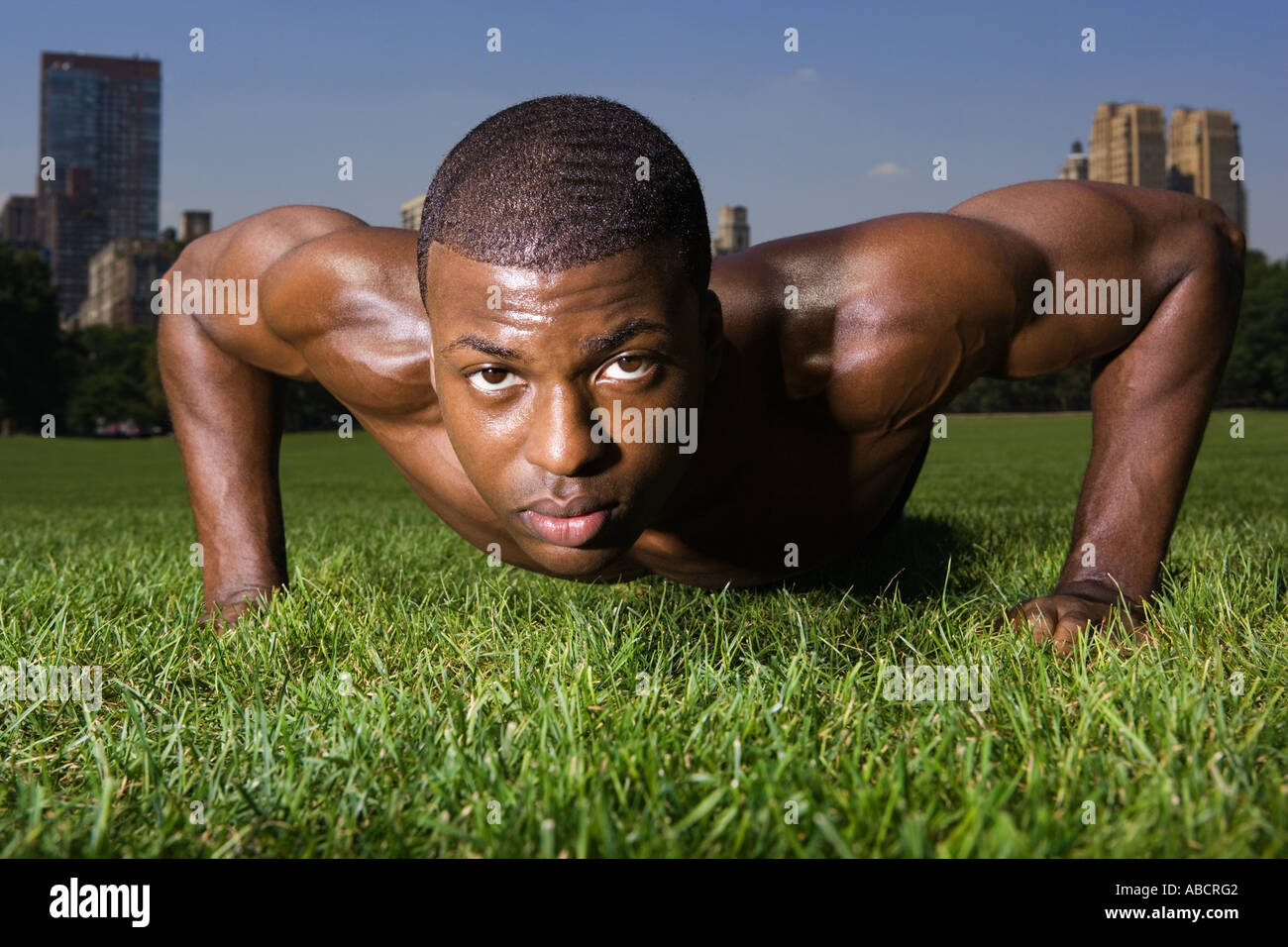 Man doing press ups in the park - Stock Image