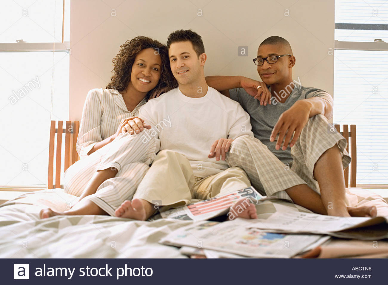 Woman and two men sitting on bed - Stock Image