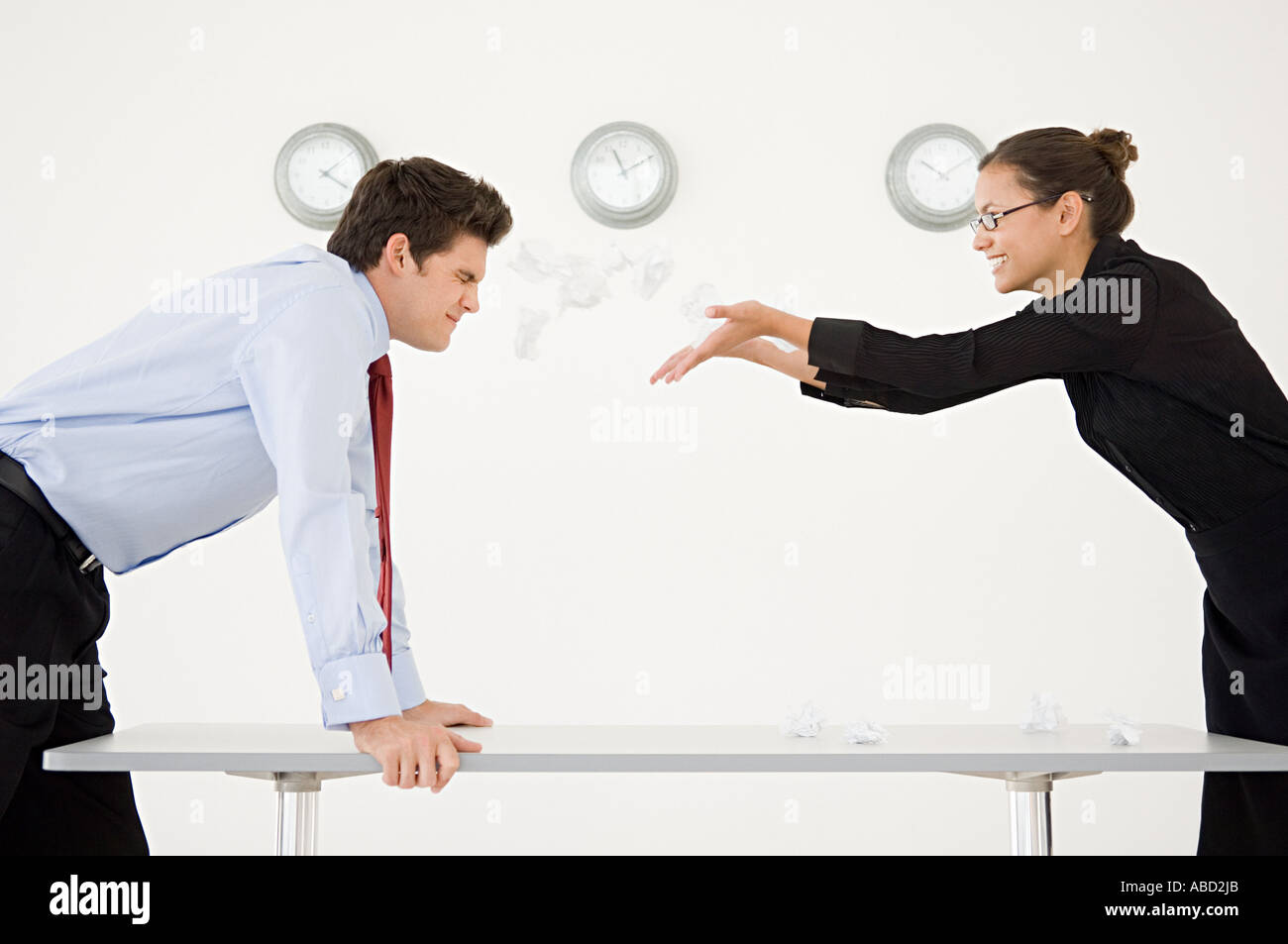Woman throwing screwed up paper at man - Stock Image