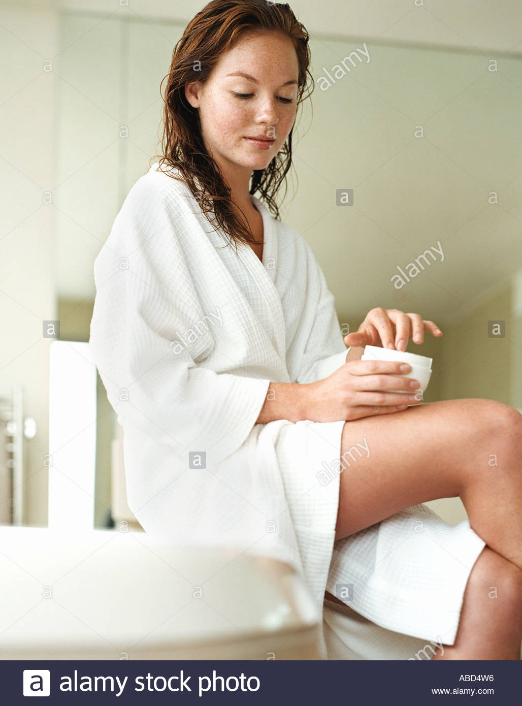 Young woman applying moisturiser - Stock Image