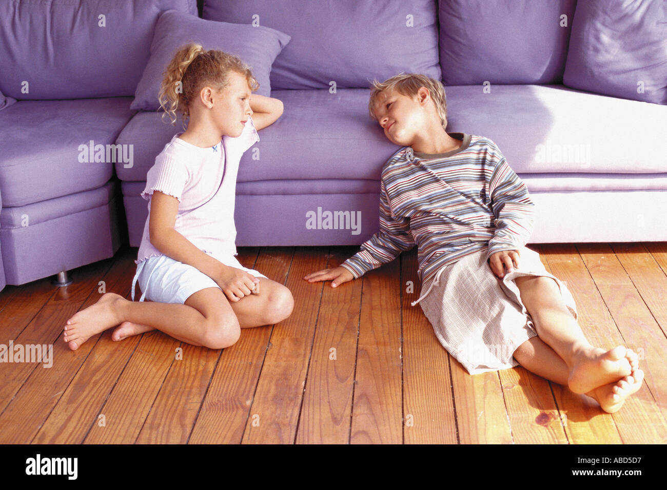 Girl and boy sitting against sofa - Stock Image