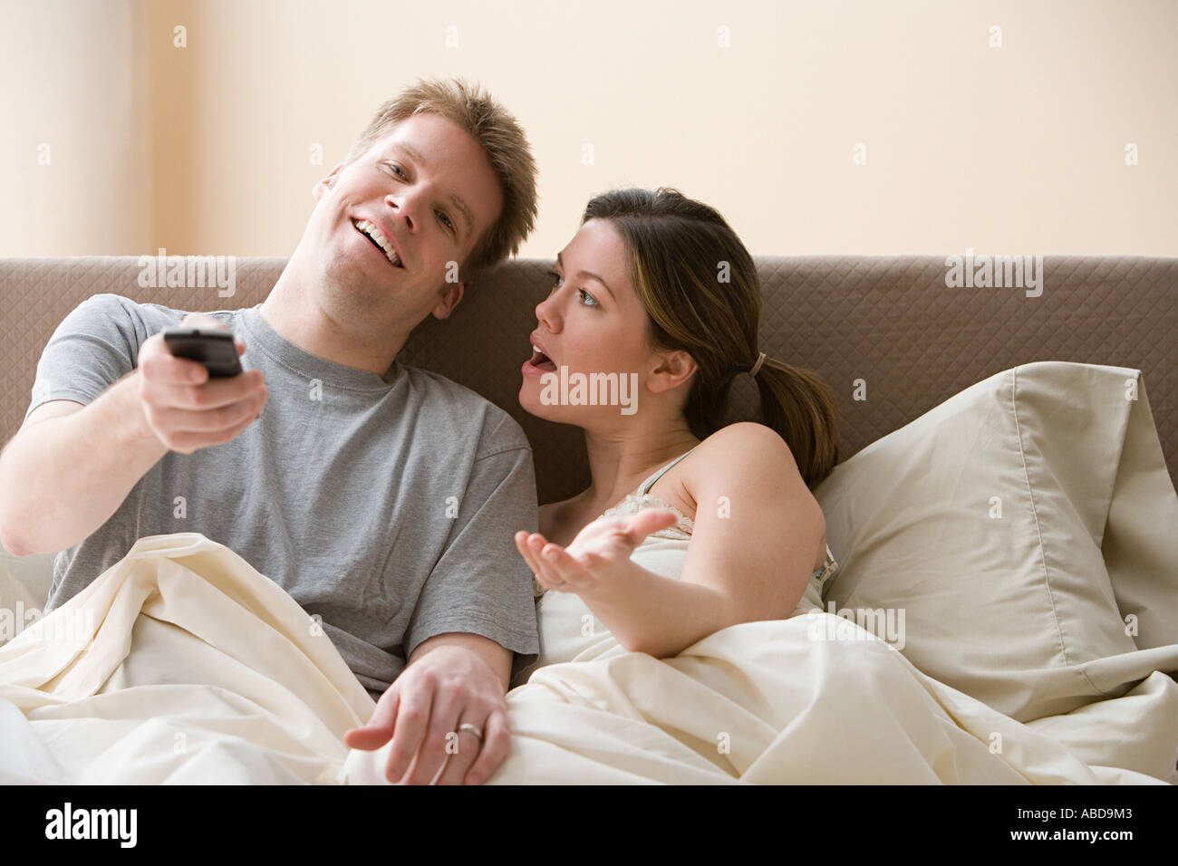 Couple watching television and arguing in bed - Stock Image