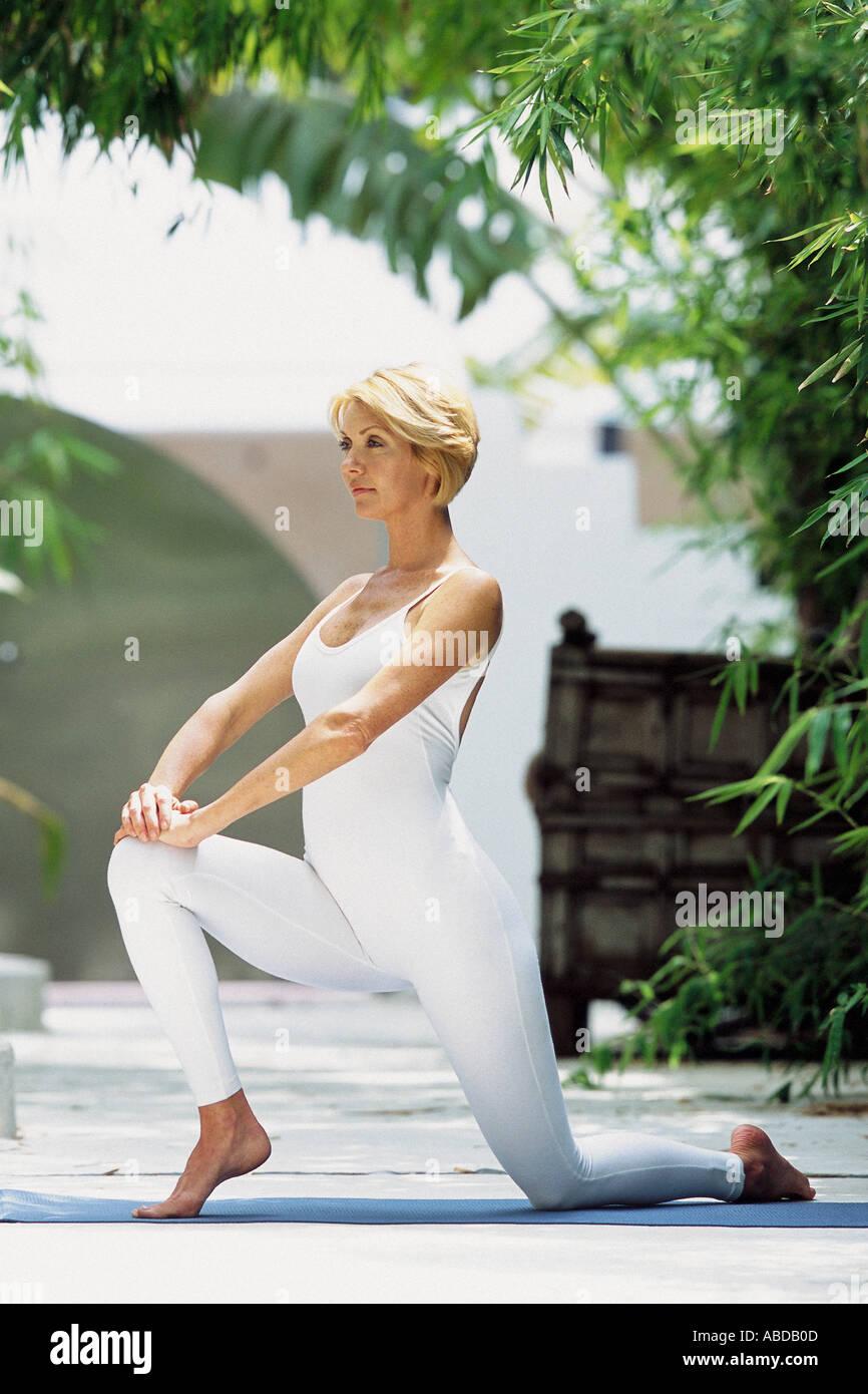 Woman doing yoga outdoors Stock Photo