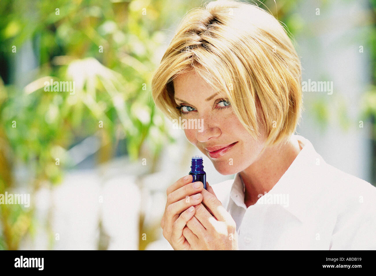 Woman smelling scent outdoors - Stock Image