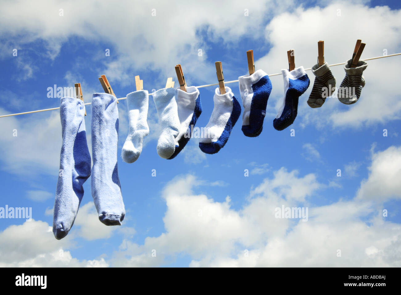 A row of freshly washed socks of assorted sizes on a linen line. - Stock Image