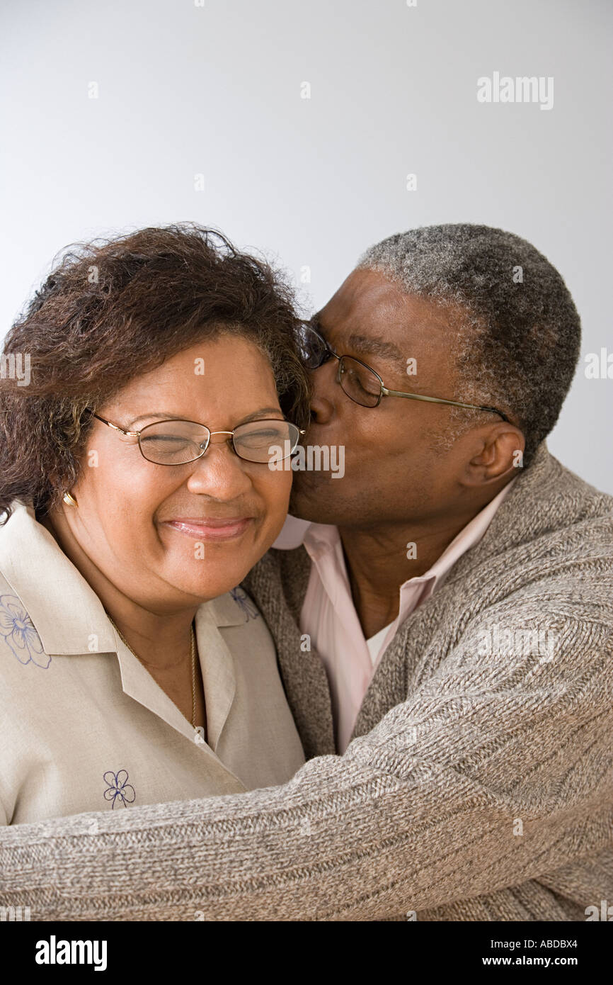 Man kissing wife on the cheek - Stock Image