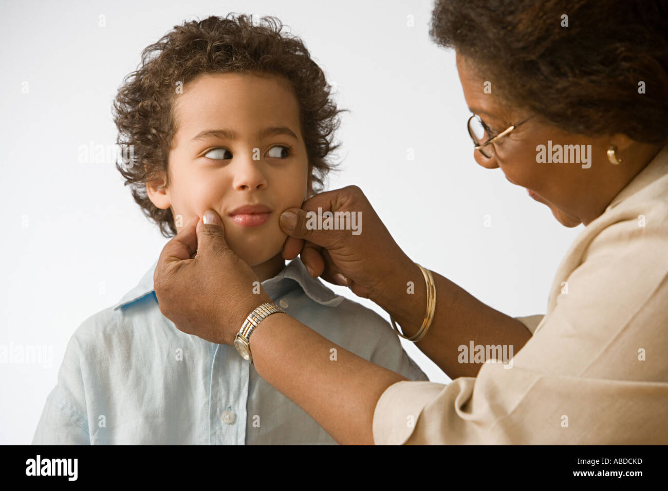 Grandmother pinching grandson's cheeks - Stock Image