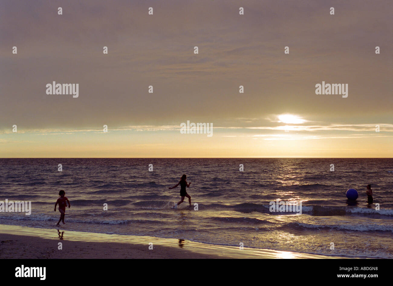 Three children playing on beach with ball near sunset Stock Photo