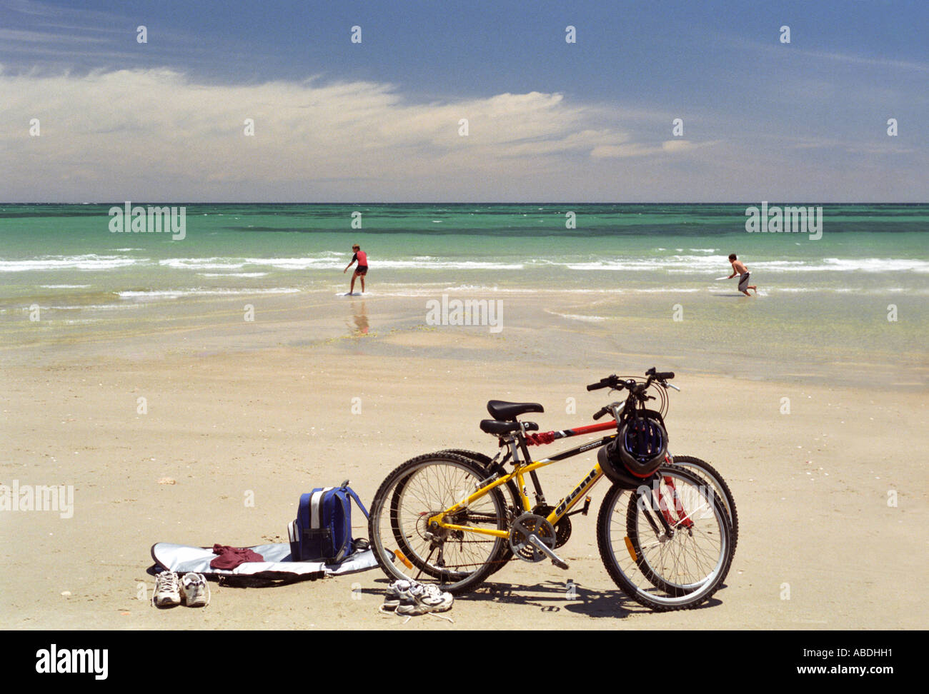 Boys playing on sandy beach bikes clothes and backpacks in foreground - Stock Image