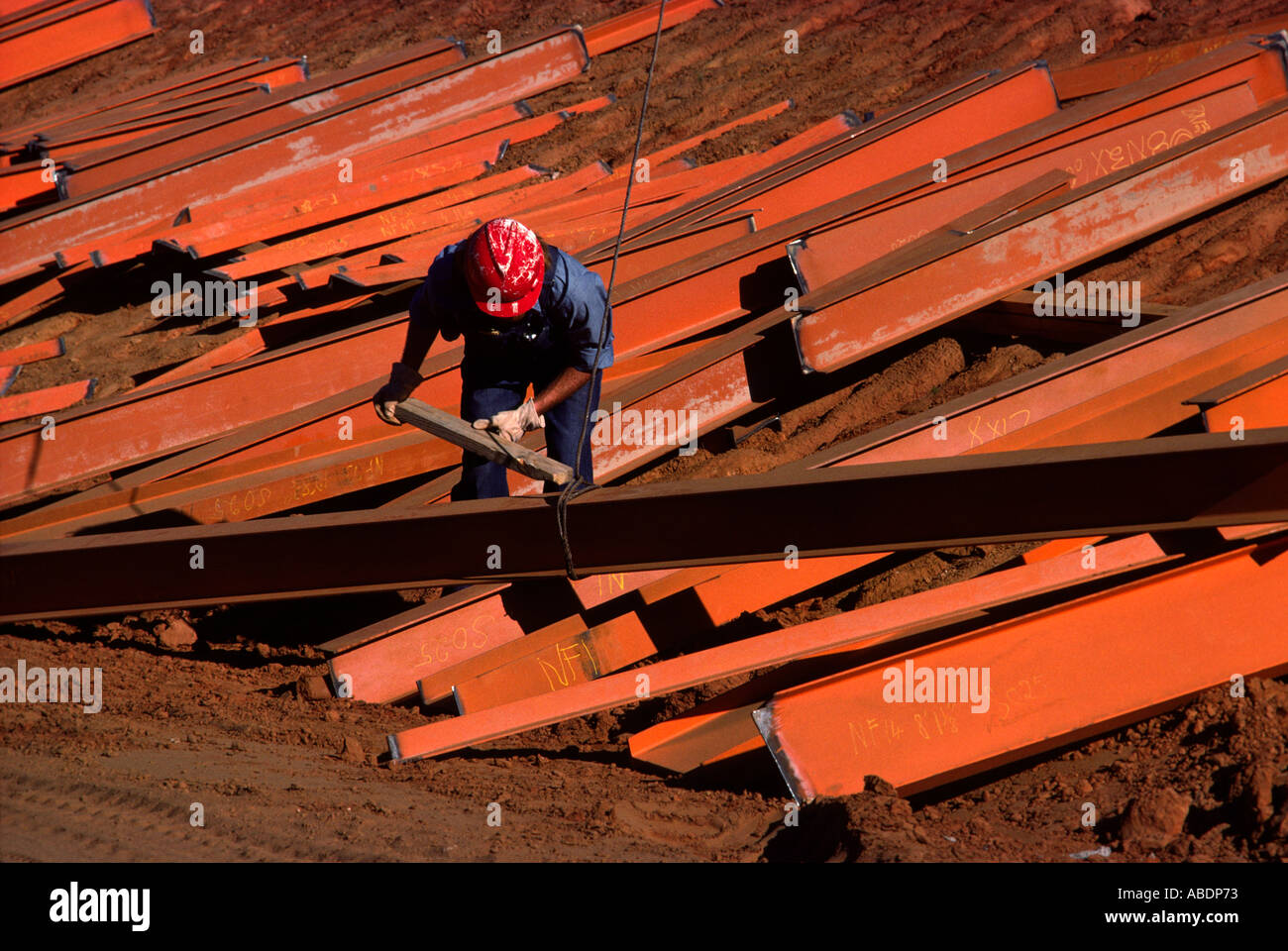 A graphic photograph of a blue collar worker about to raise up a steel beam - Stock Image