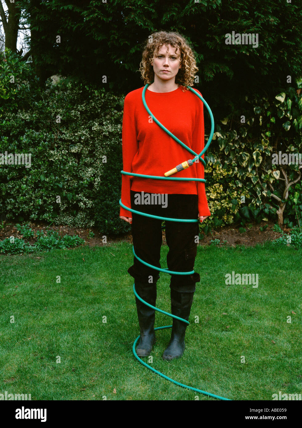 Woman wrapped in a hosepipe - Stock Image