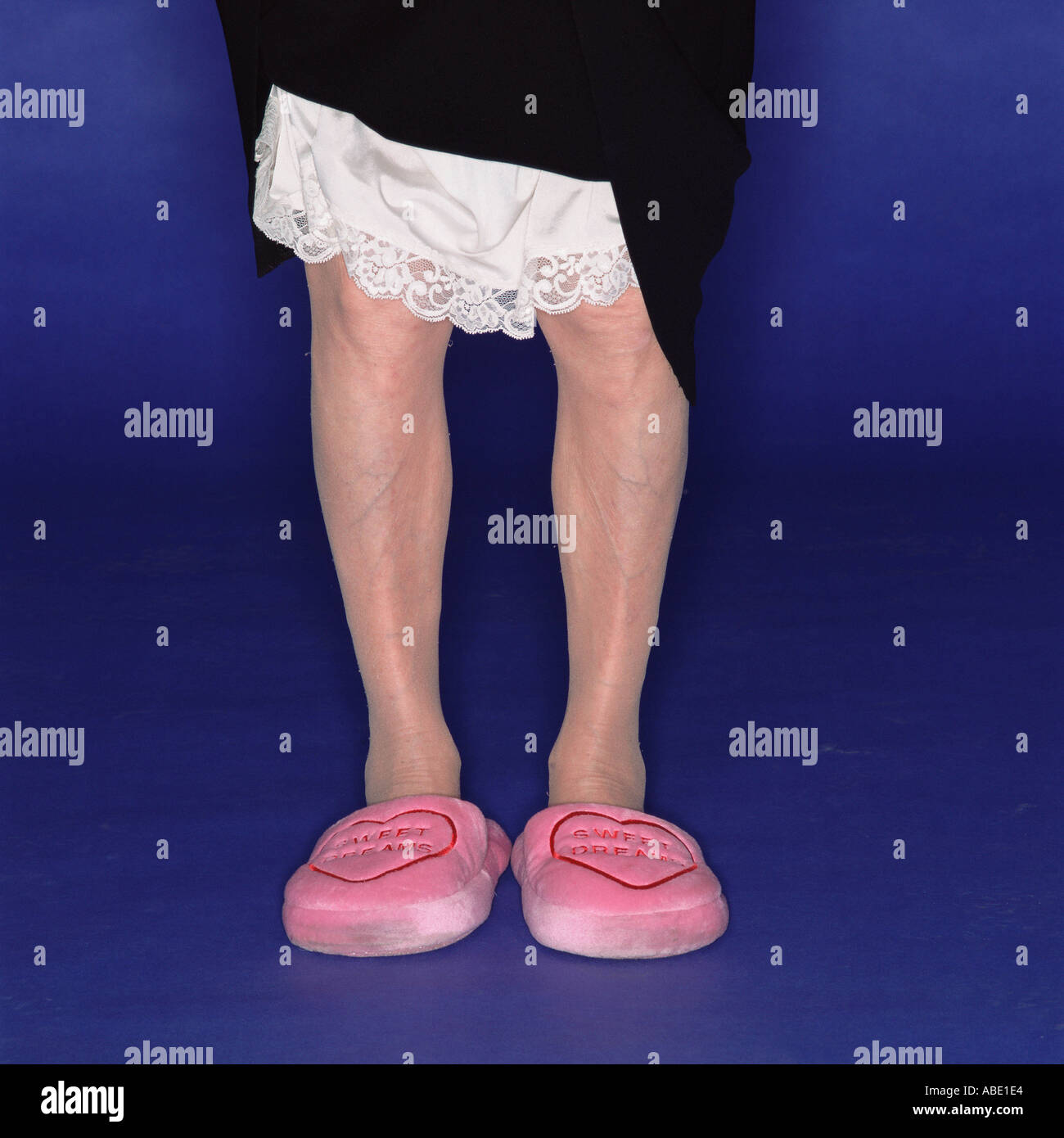 Grandmother in comfy pink slippers - Stock Image