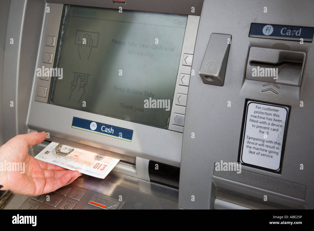 ATM cashpoint cash machine Hole in the Wall bank teller remove money screen with a pensioner's hand taking £10 sterling notes. England UK Britain Stock Photo