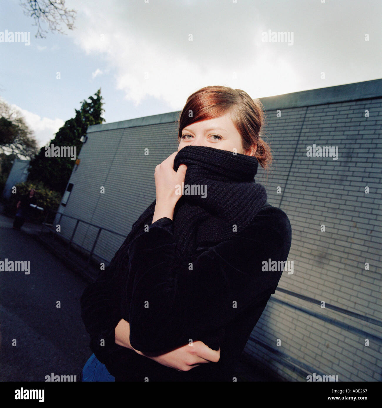 Girl covering her face with wool scarf - Stock Image
