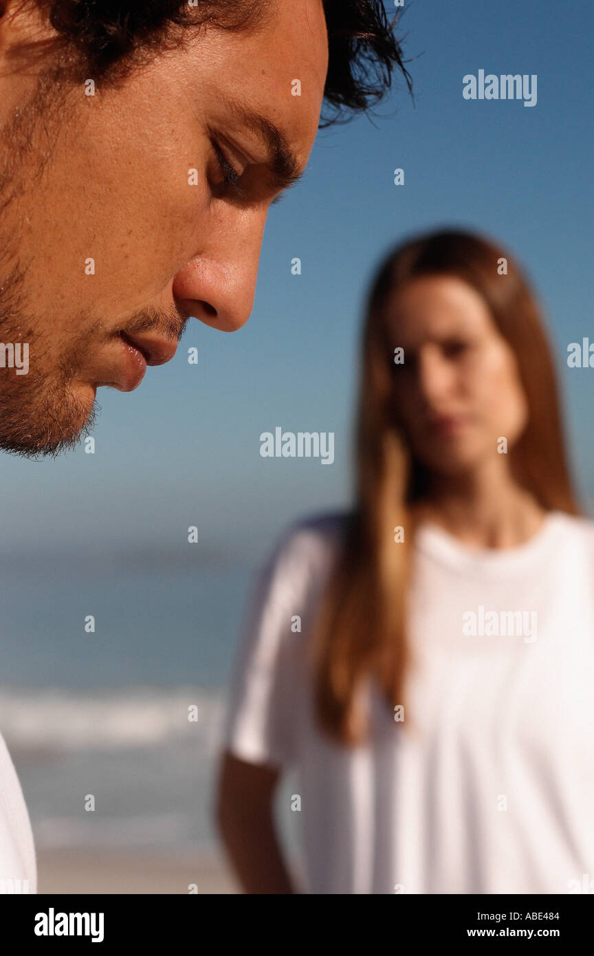 Profile of a man with a woman in the background - Stock Image