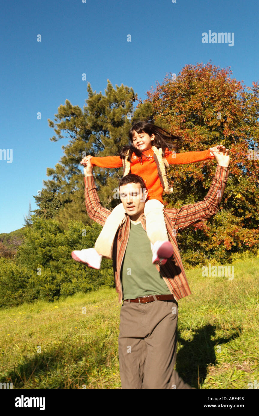 Father shoulder carrying daughter Stock Photo
