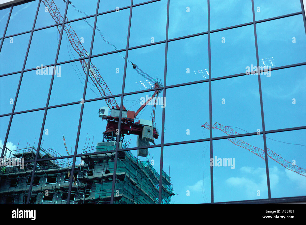 Reflection of construction crane on glass - Stock Image