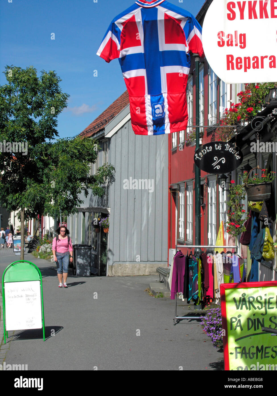 Trondheim storefronts facades of old timber houses woodhouses with advertising shield for bike bicycle shop with trikot jersey - Stock Image