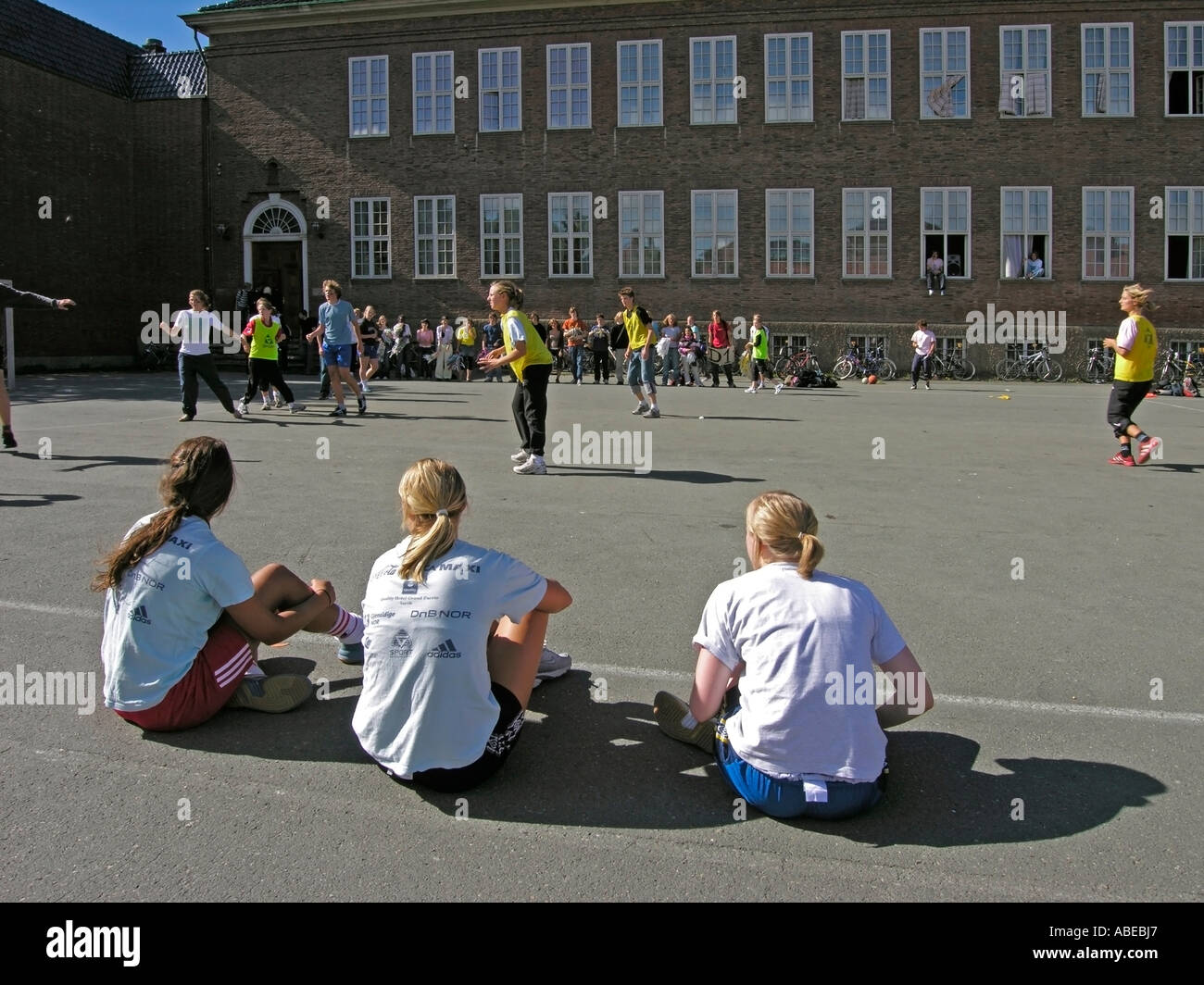 young people teenies about 13 to 17 years old making sport on schoolyard in summer three girls sitting on ground Stock Photo