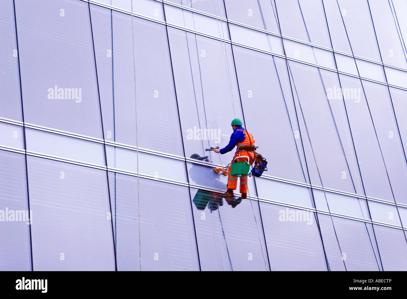 window cleaner suspended on wires at multistorey office block, Glasgow city centre, Scotland - Stock Image