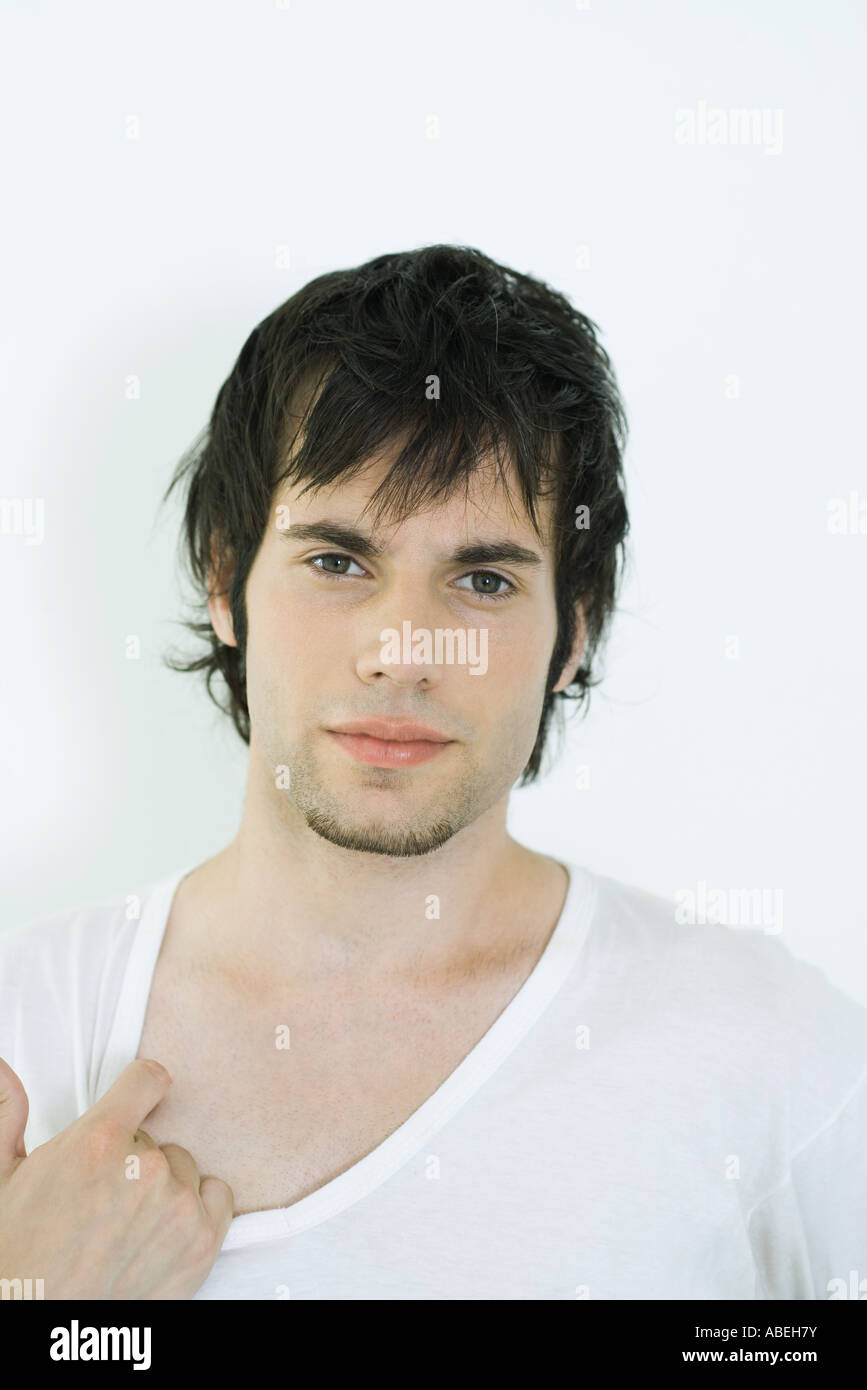 Young man wearing tee-shirt, pulling on collar, portrait - Stock Image