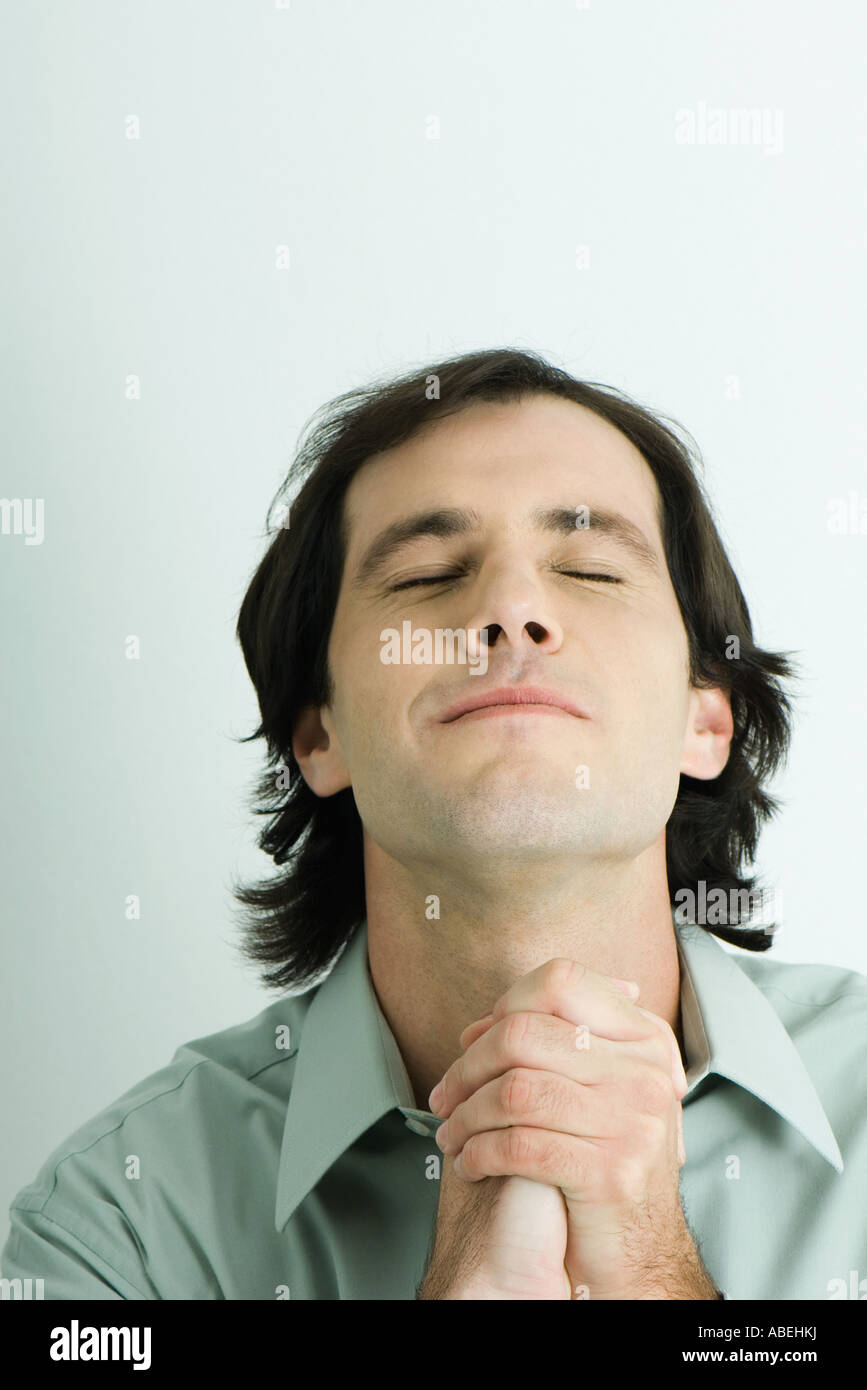Man clasping hands, head back and eyes closed, head and shoulders, portrait - Stock Image
