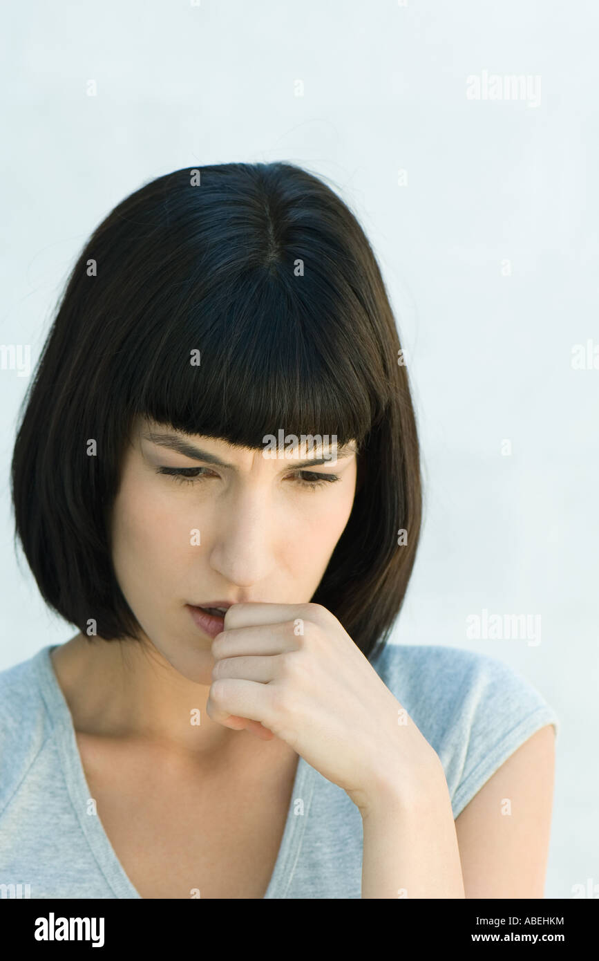 Woman biting thumb and looking down, head and shoulders, portrait - Stock Image