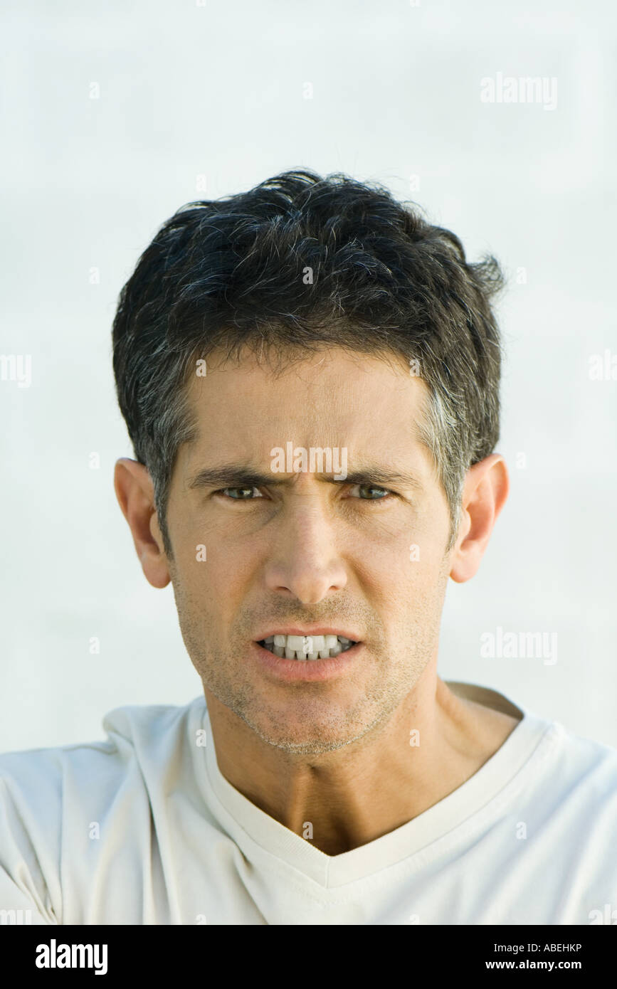 Man scowling at camera, head and shoulders, portrait - Stock Image