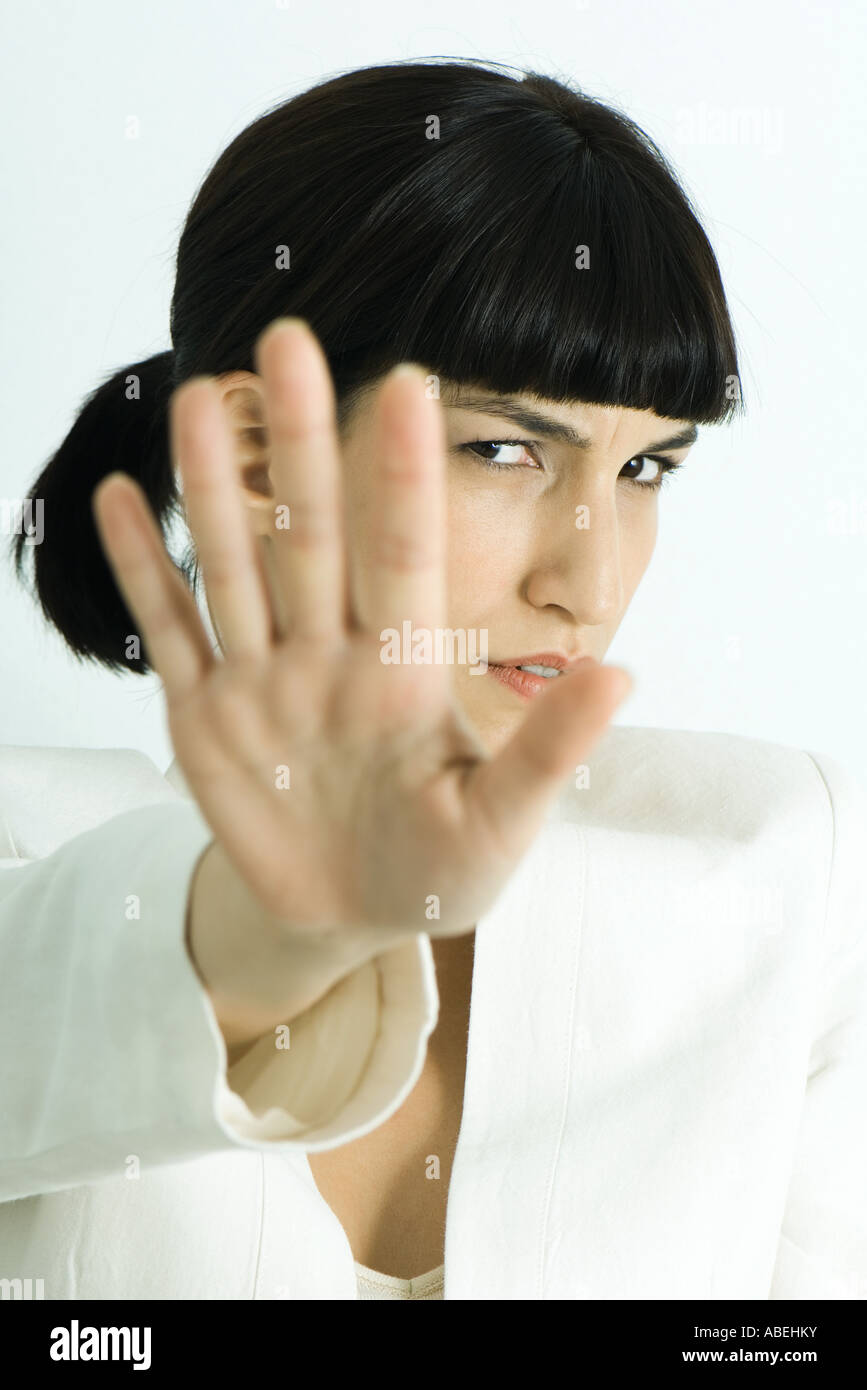 Woman holding out palm of hand to camera, scowling, head and shoulders, portrait - Stock Image