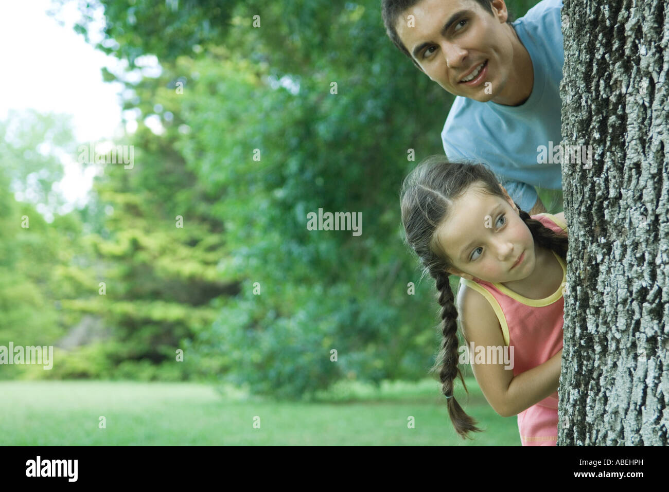 Father and daughter peeking around tree trunk Stock Photo