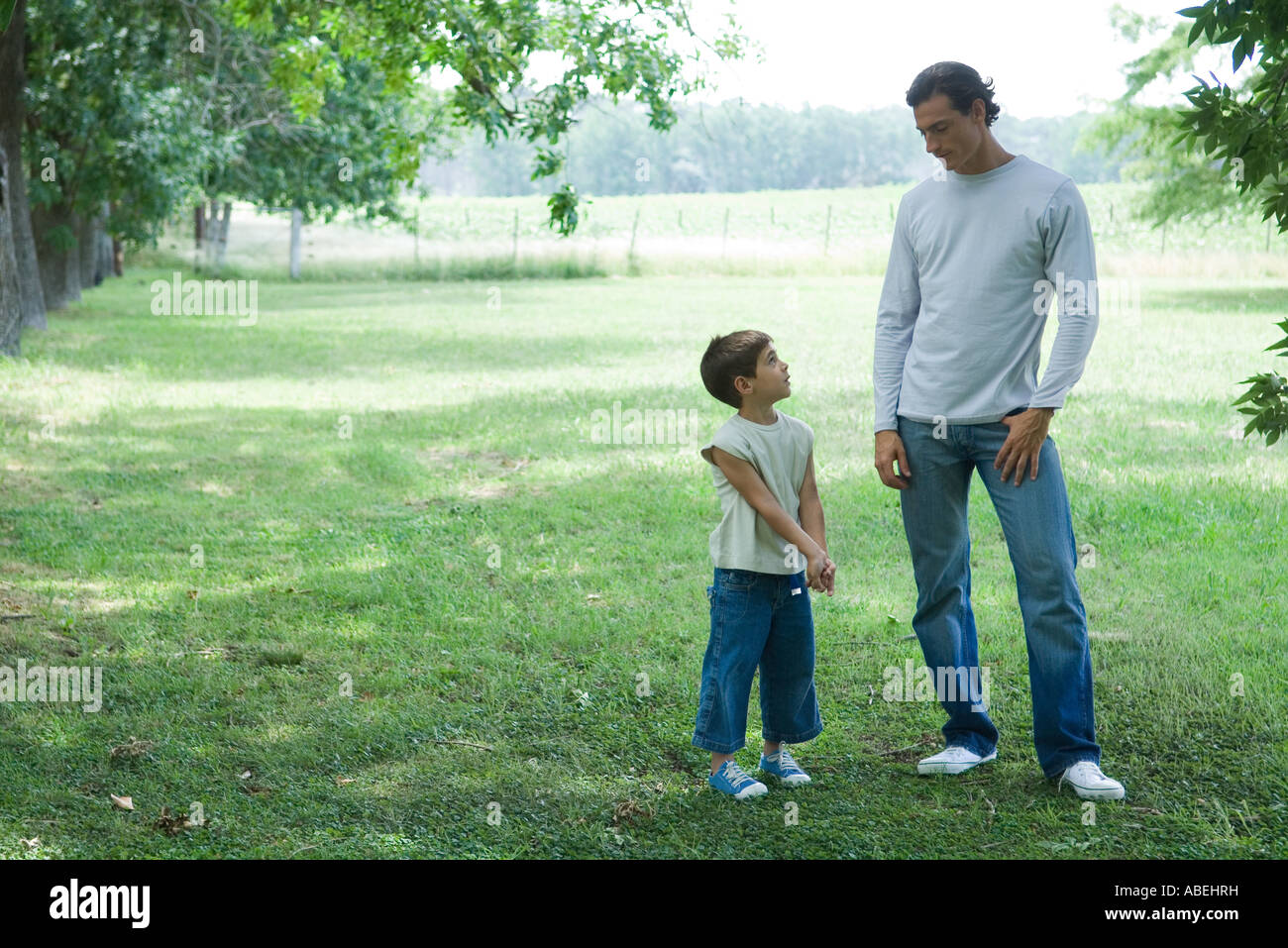 Father and son standing outside on grass, looking at each other - Stock Image
