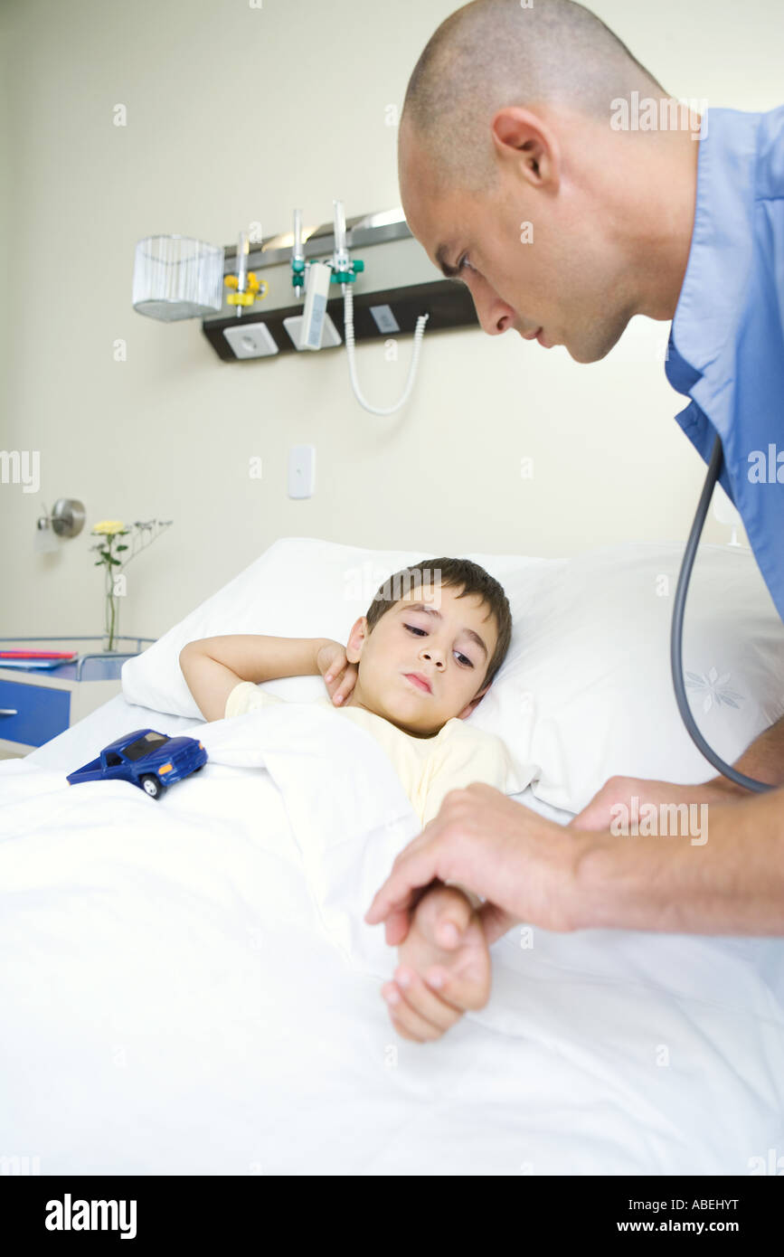 Boy lying in hospital bed, intern holding boy's arm Stock Photo