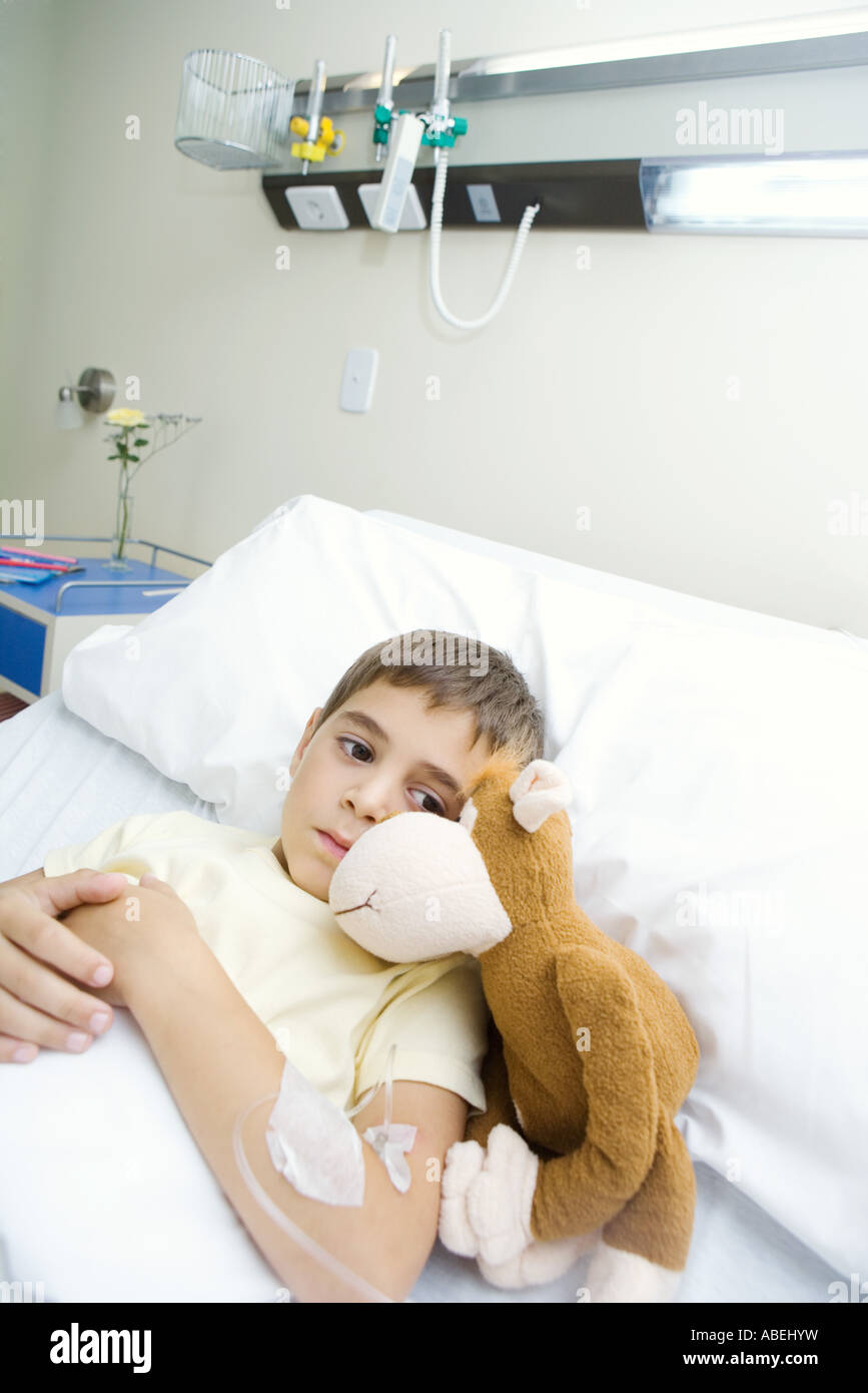 Boy lying in hospital bed next to stuffed animal Stock Photo