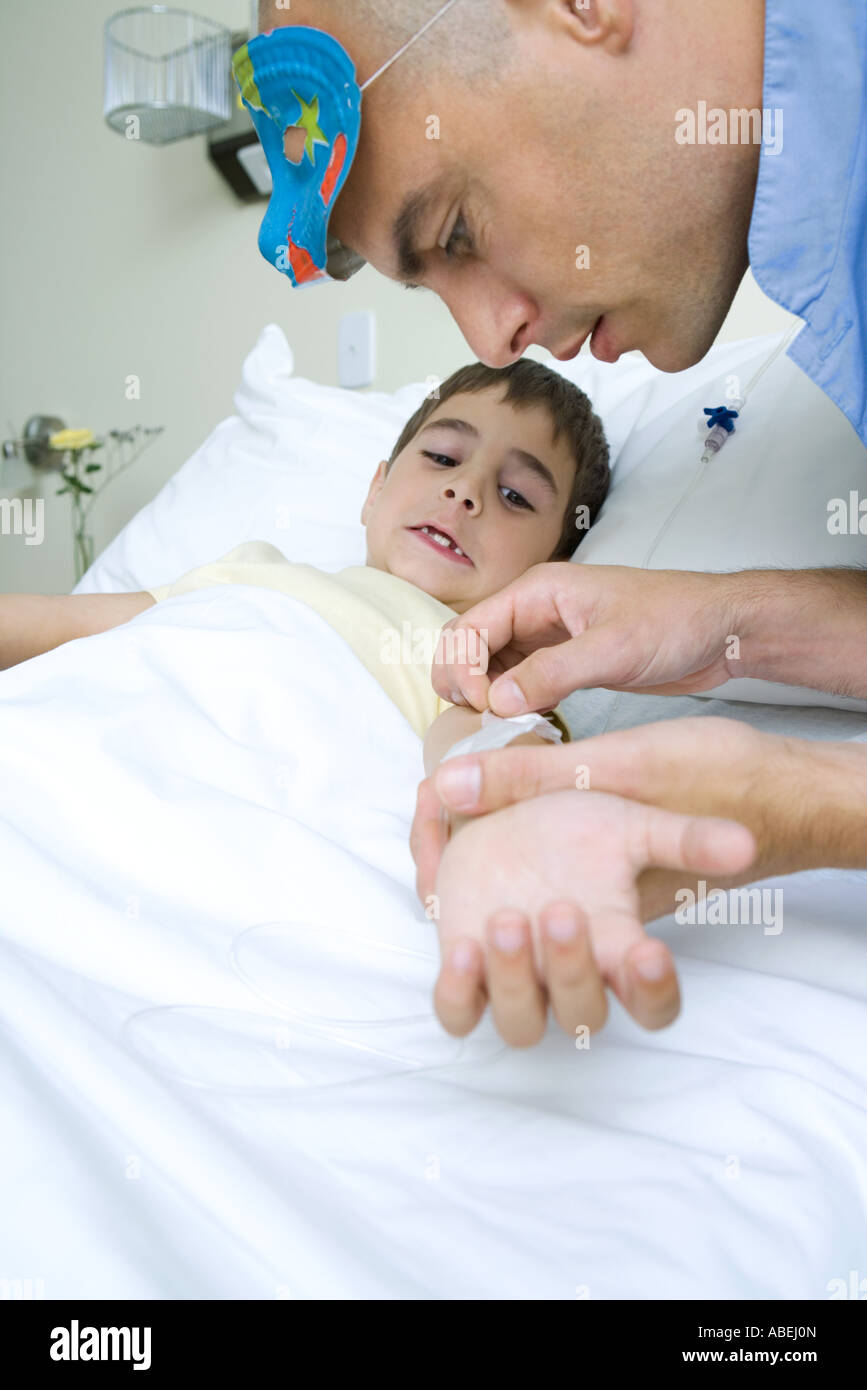 Boy lying in hospital bed, intern wearing mask on head removing adhesive tape from boy's arm Stock Photo