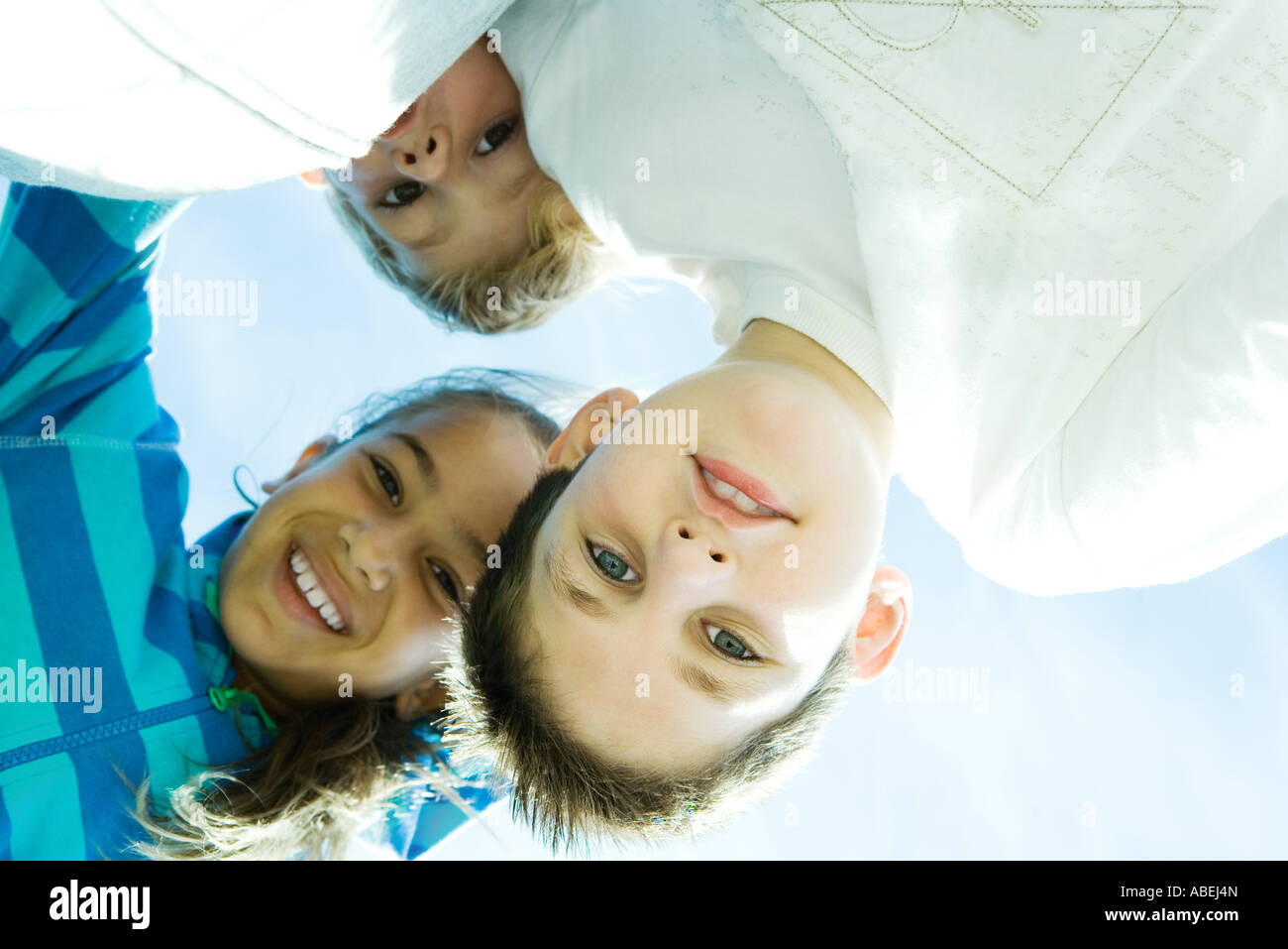 Children smiling at camera, view from directly below - Stock Image