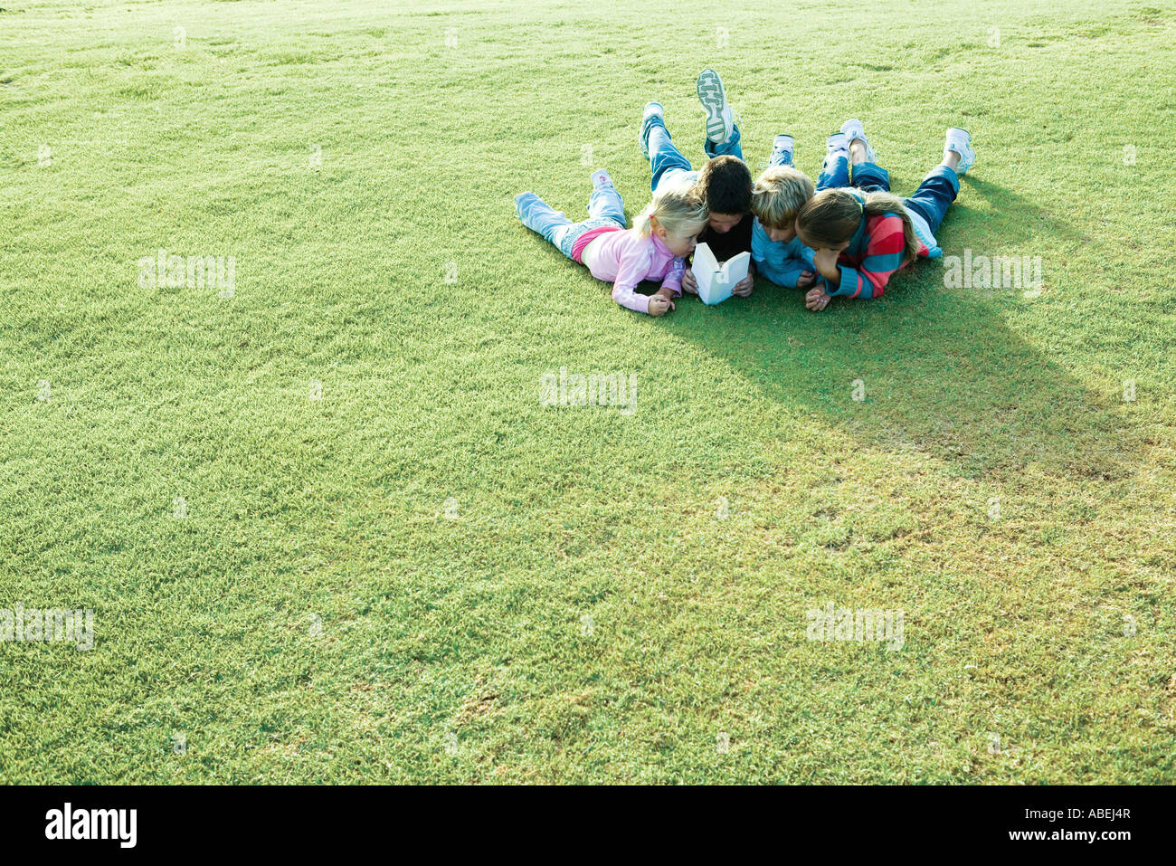 Children lying on grass, reading book together - Stock Image