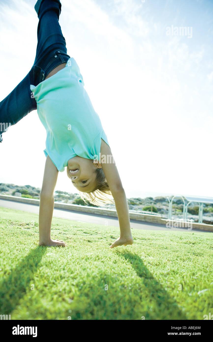 Girl doing cartwheel on grass - Stock Image