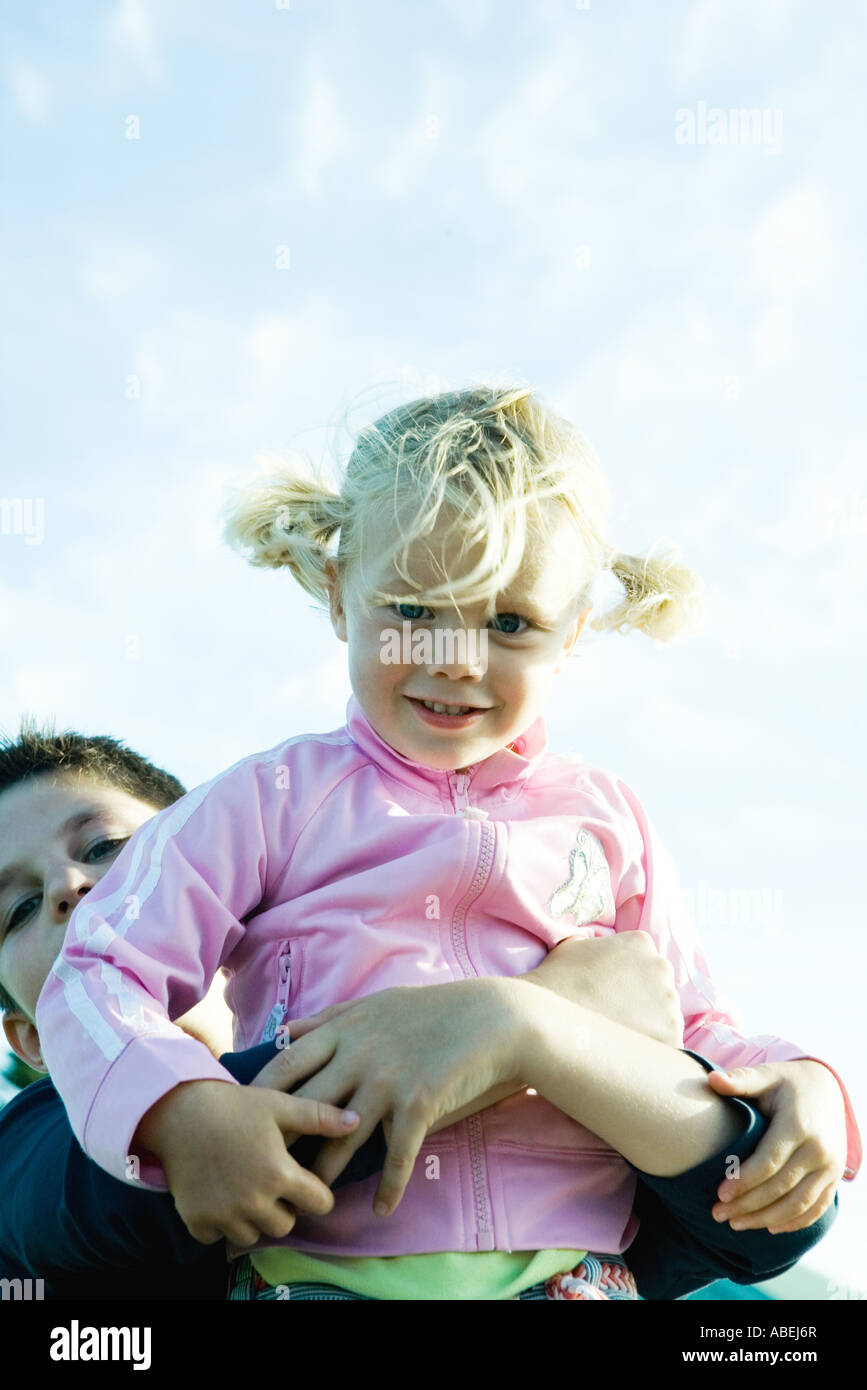 Boy holding up little girl, low angle view - Stock Image