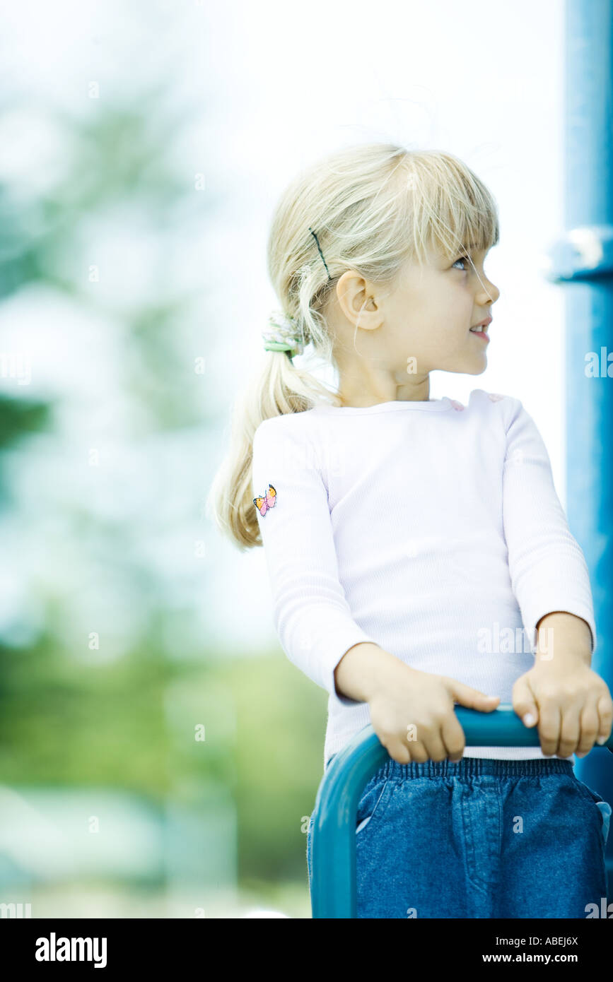 Girl on playground equipment, looking up - Stock Image