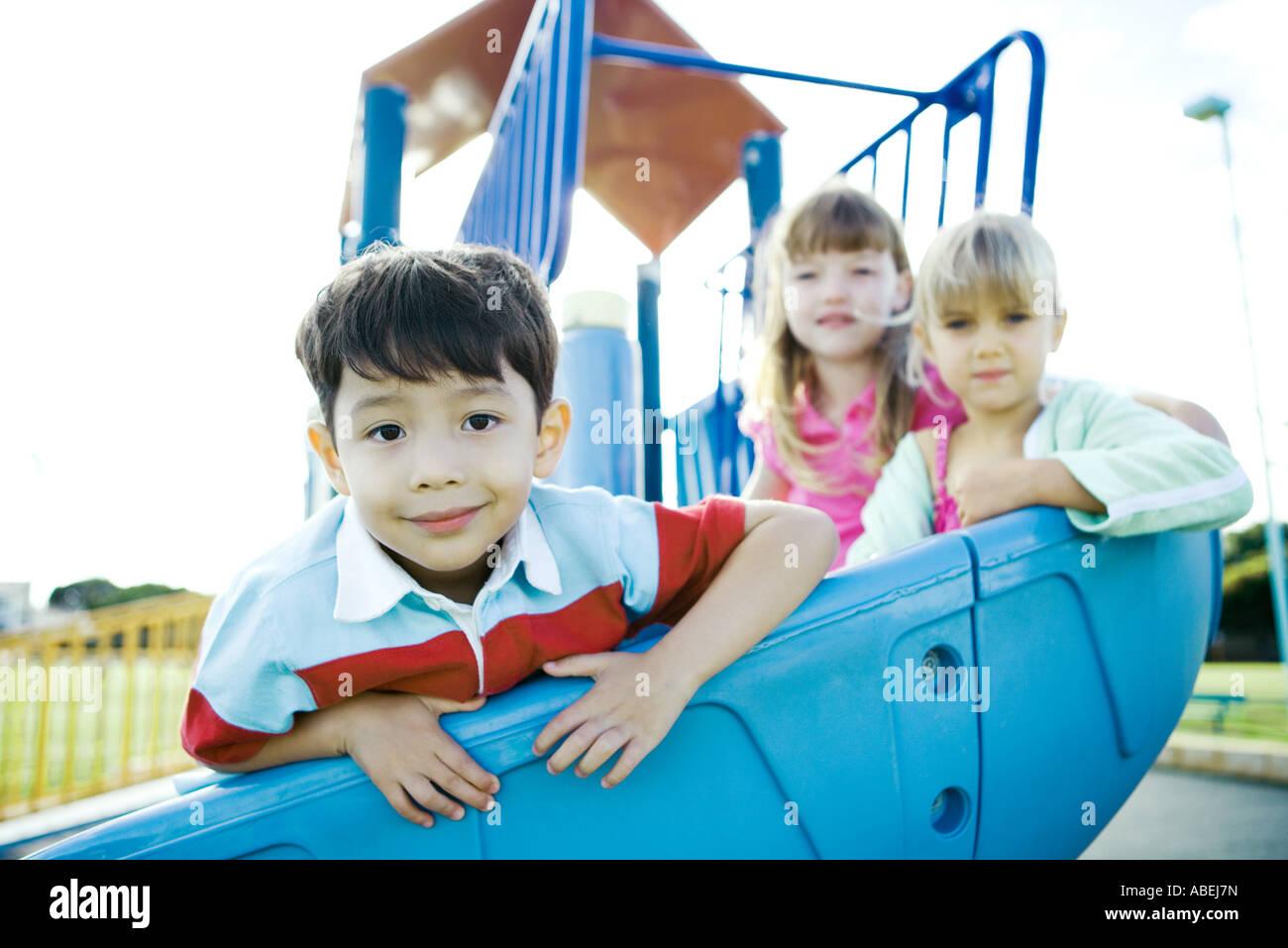 Children on playground equipment, smiling at camera Stock Photo